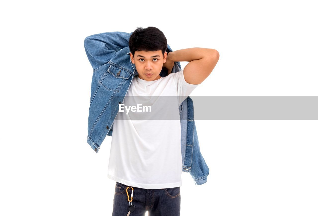 Portrait of young man wearing denim jacket while standing against white background