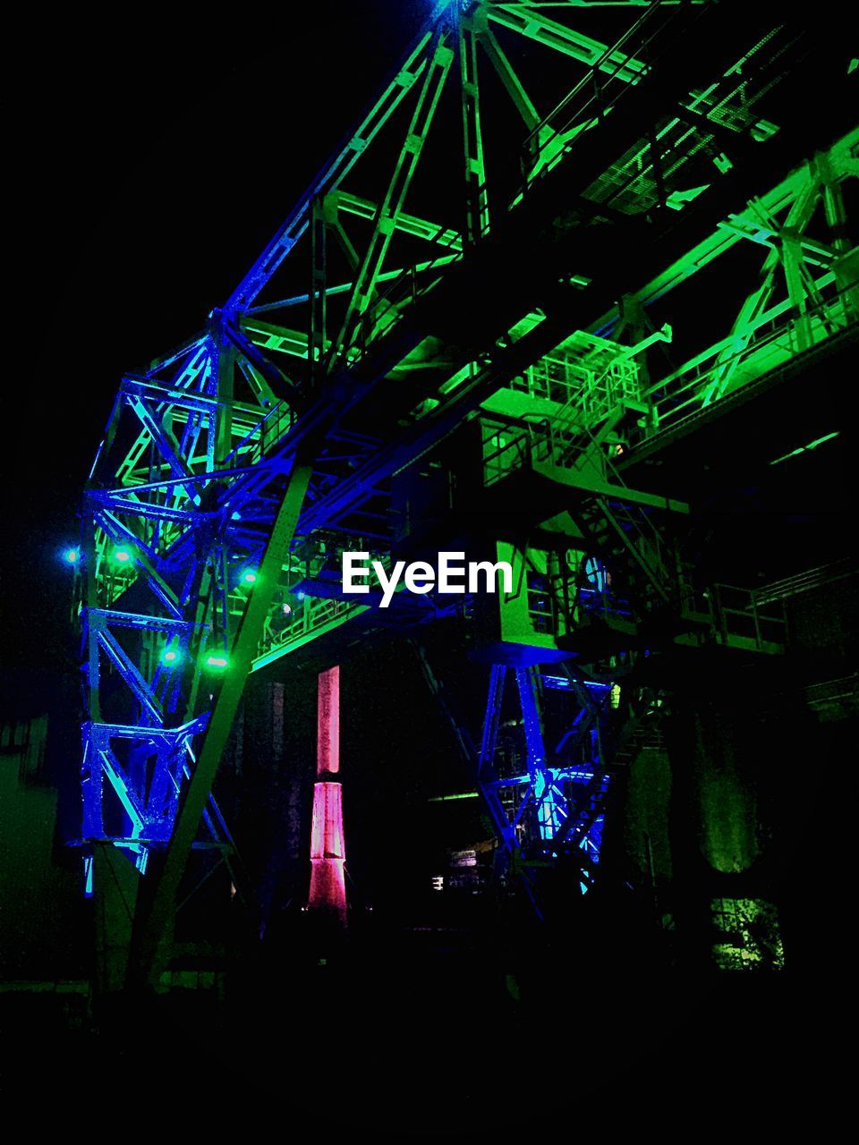 illuminated, night, low angle view, arts culture and entertainment, green color, built structure, stage light, no people, laser, performance, nightlife, stage - performance space, architecture, neon, indoors