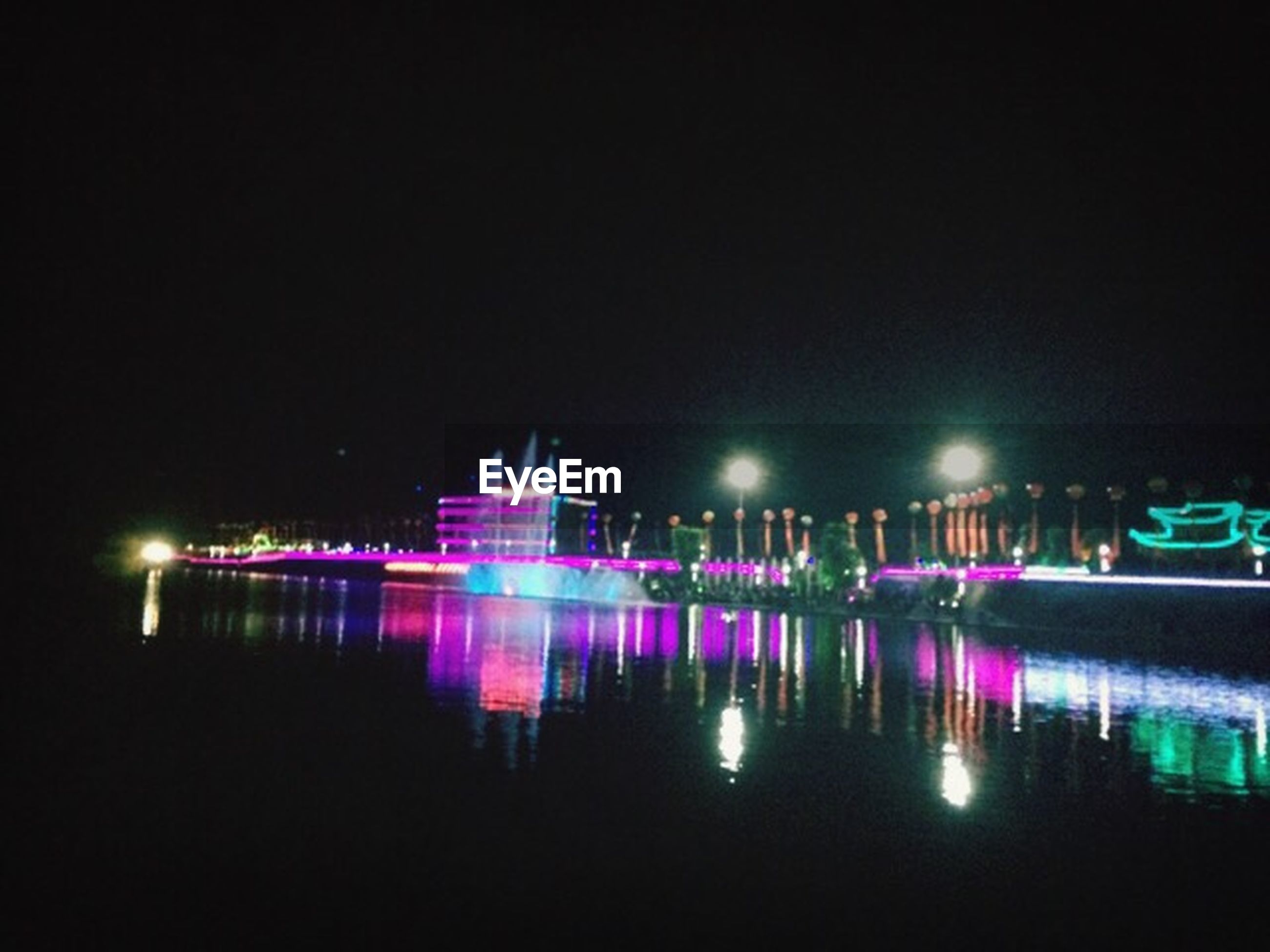 illuminated, night, water, reflection, waterfront, copy space, long exposure, multi colored, building exterior, city, architecture, clear sky, built structure, light - natural phenomenon, lighting equipment, no people, glowing, motion, outdoors, blue