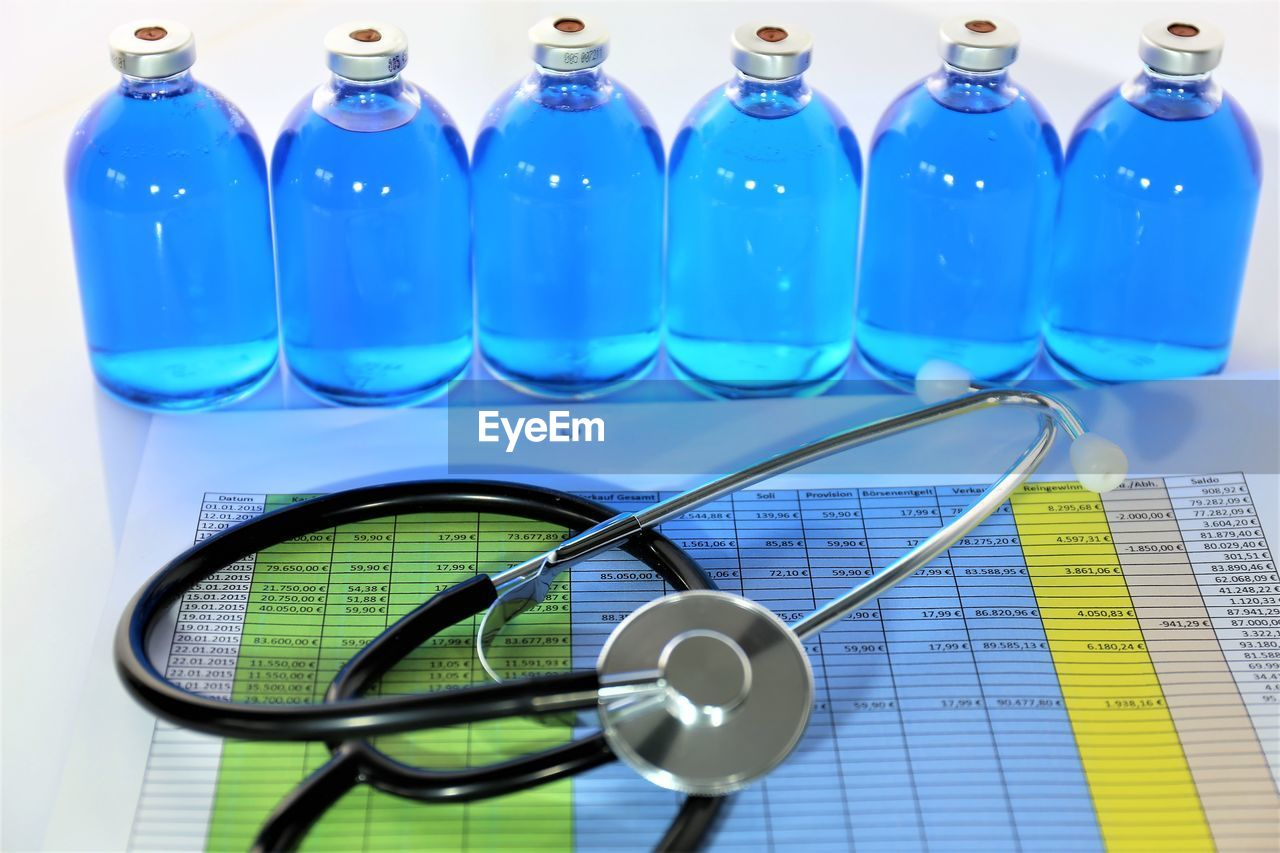Close-up of stethoscope and liquid bottles with chart on table