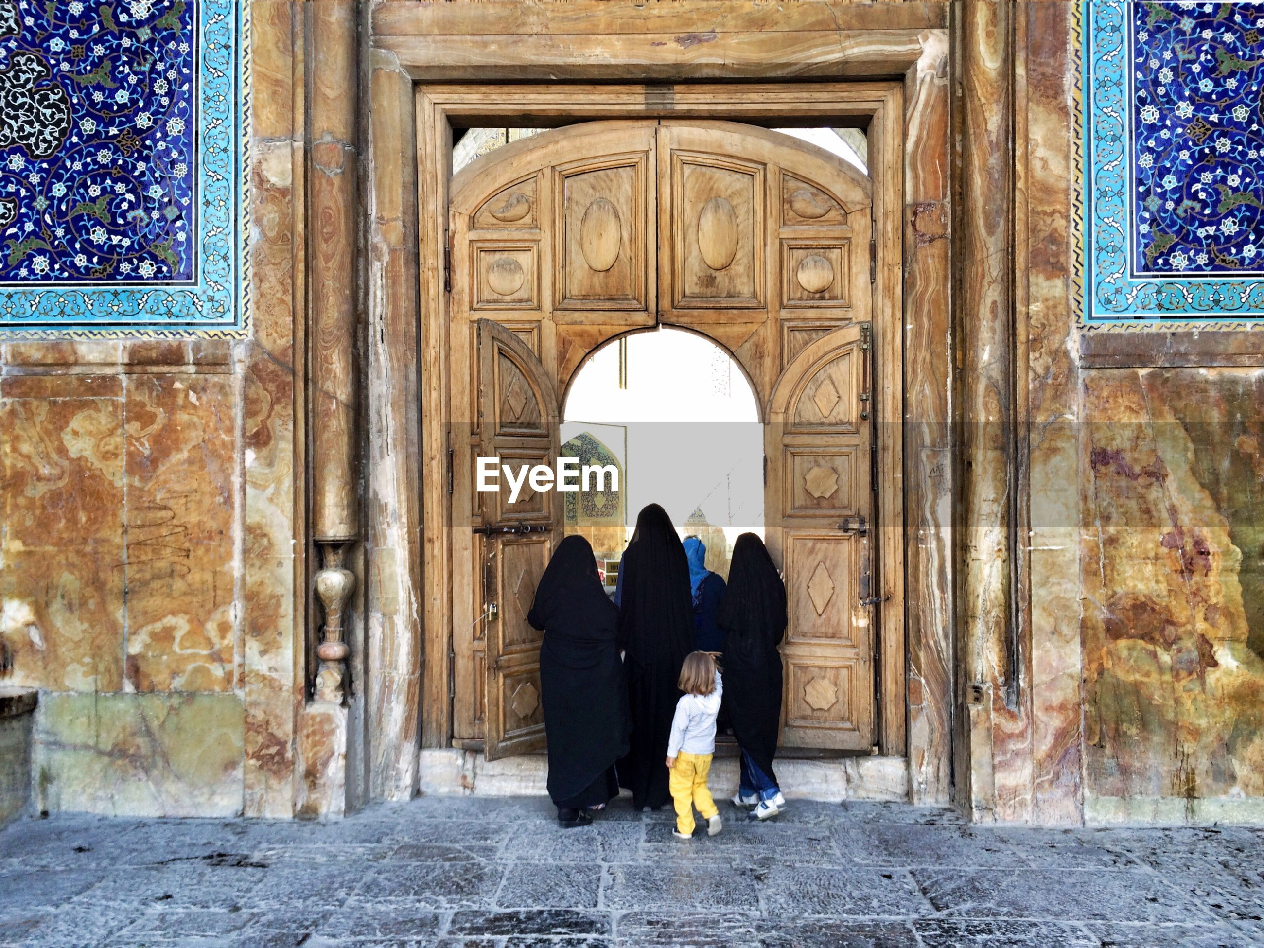 Rear view of women with child at entrance of mosque