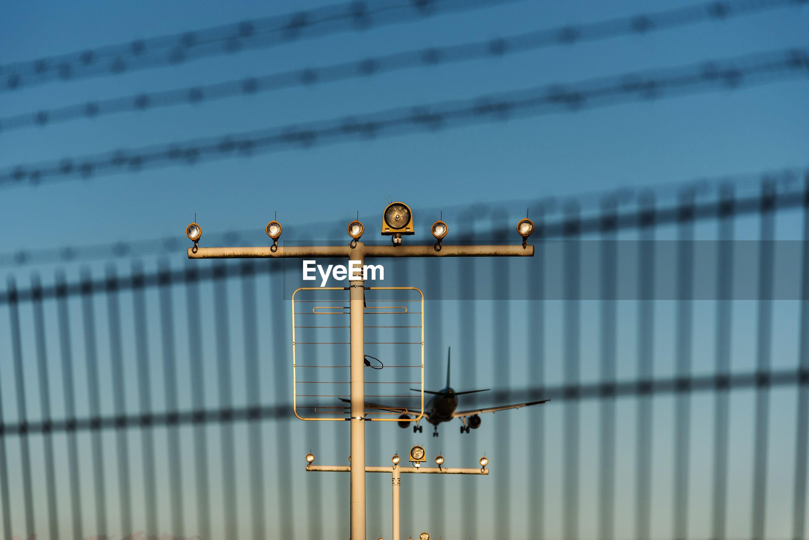 Landling passenger aircraft seen through security fence at airport