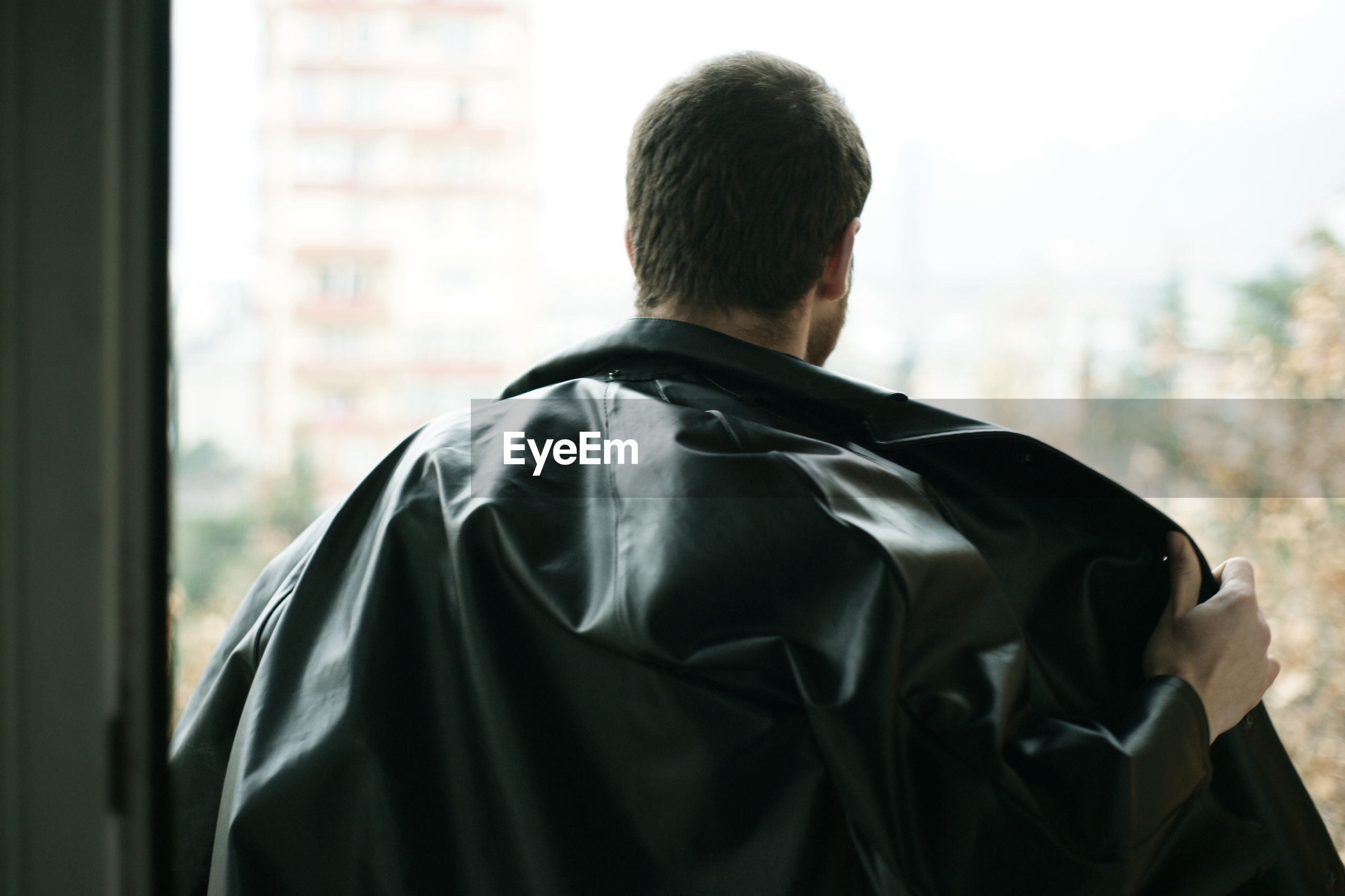 Rear view of man removing black leather jacket by window