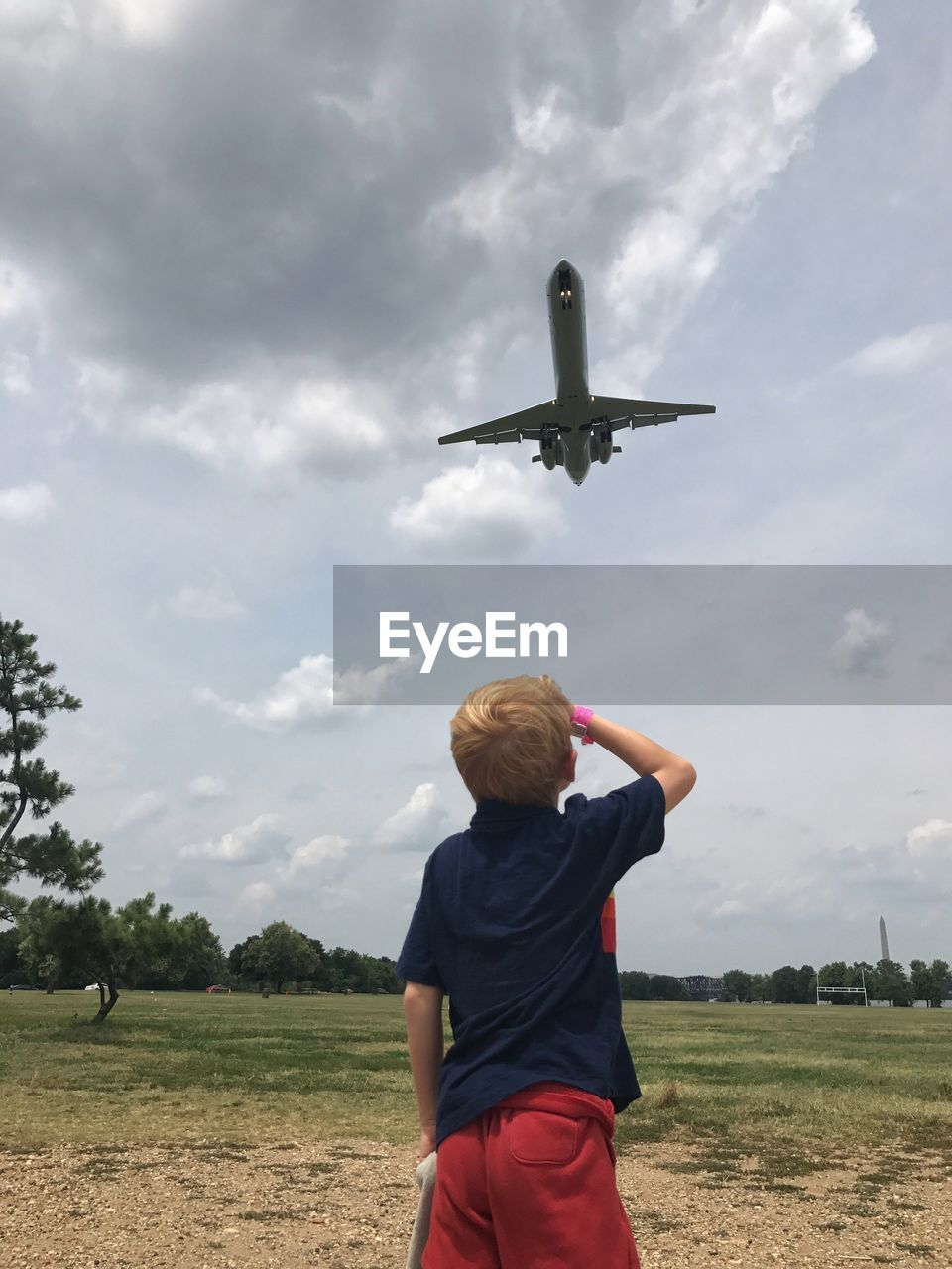 Rear View Of Boy Looking At Airplane While Standing On Field