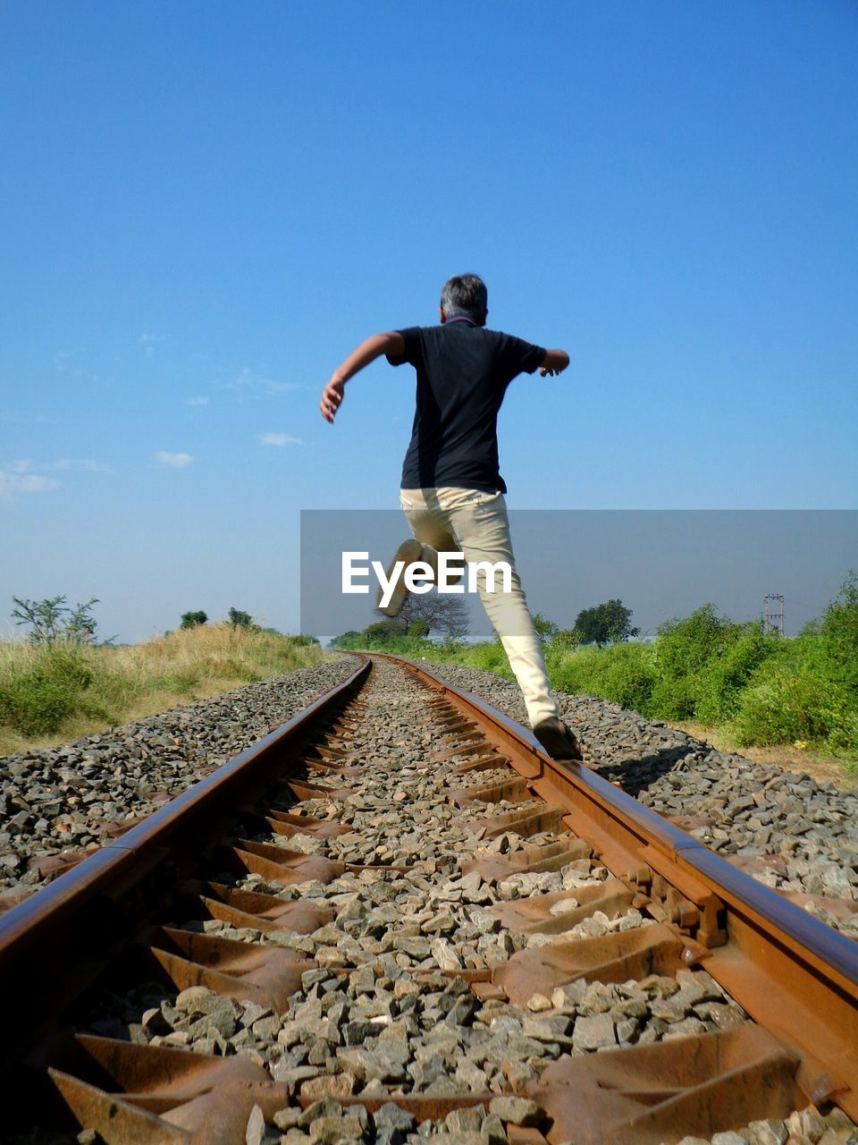 railroad track, rail transportation, transportation, full length, clear sky, day, one person, sky, the way forward, outdoors, real people, nature