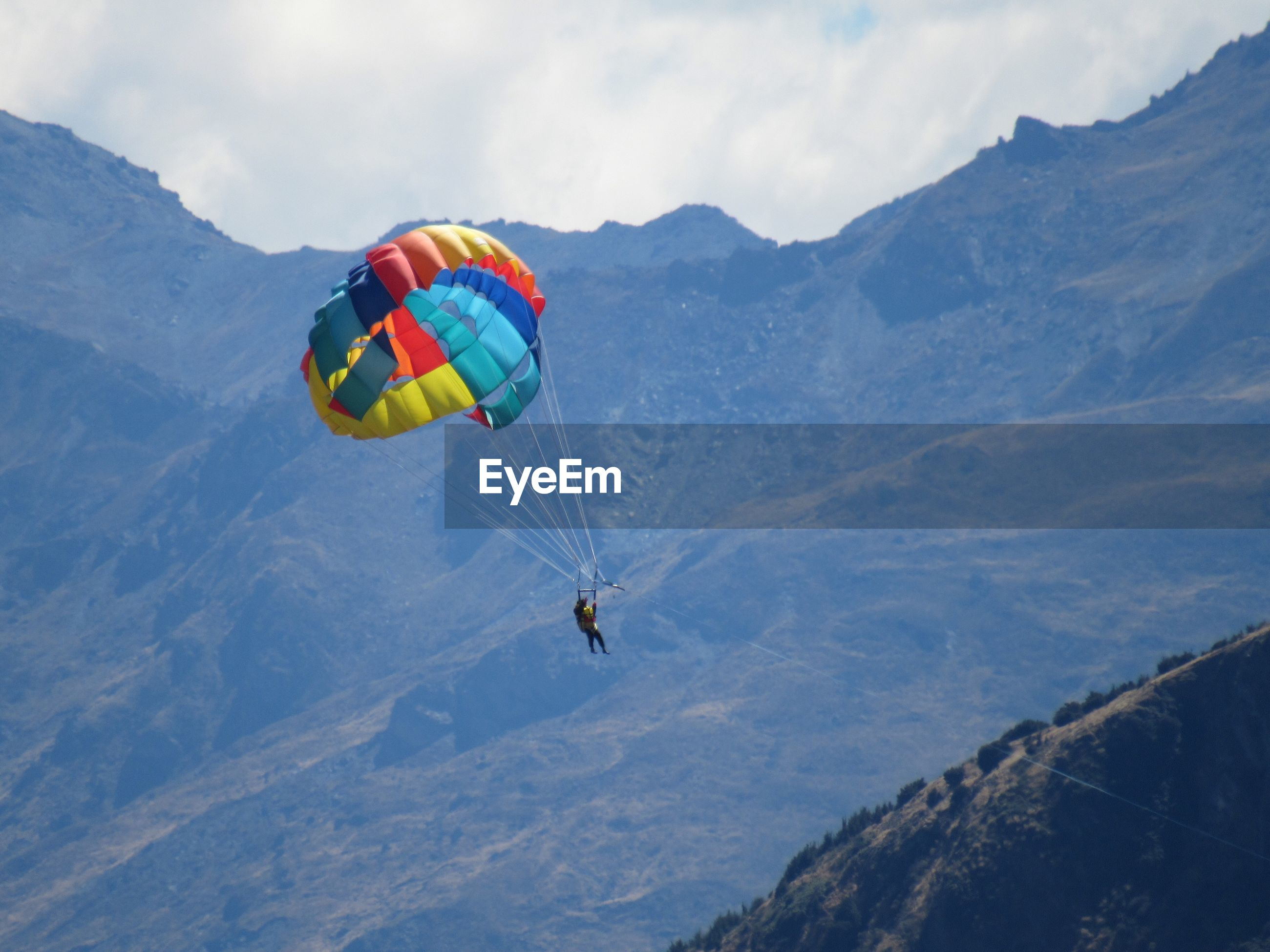 PEOPLE PARAGLIDING AGAINST MOUNTAIN