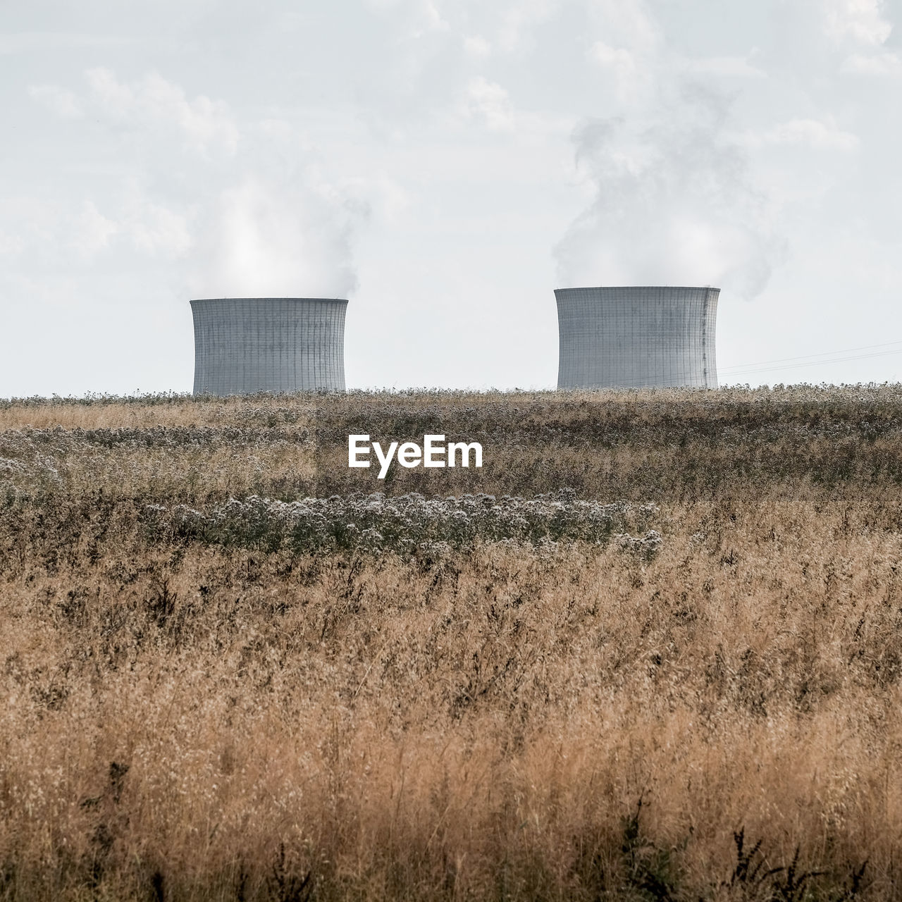Cooling towers on grassy landscape against sky