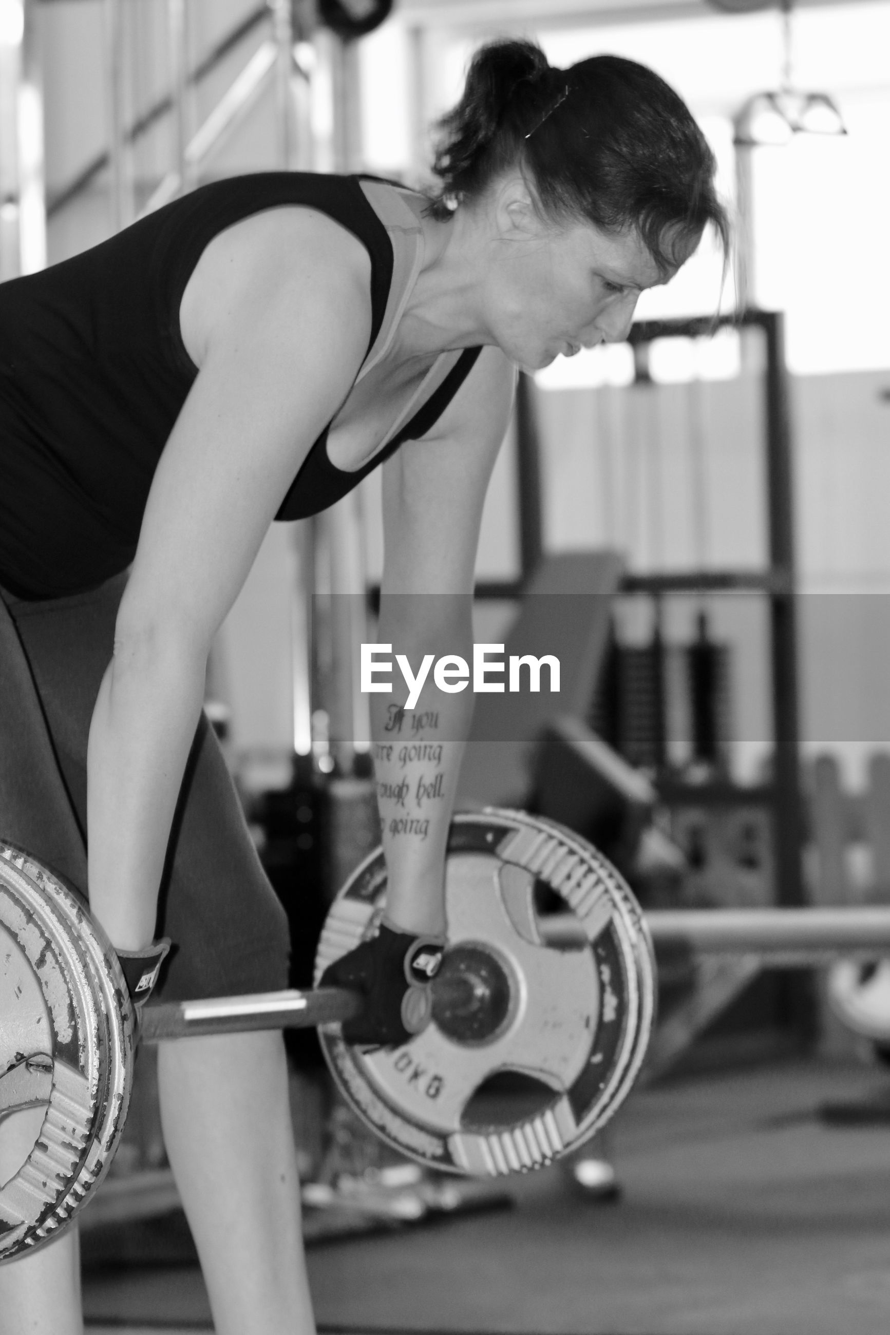 Mature woman holding barbell while exercising in gym