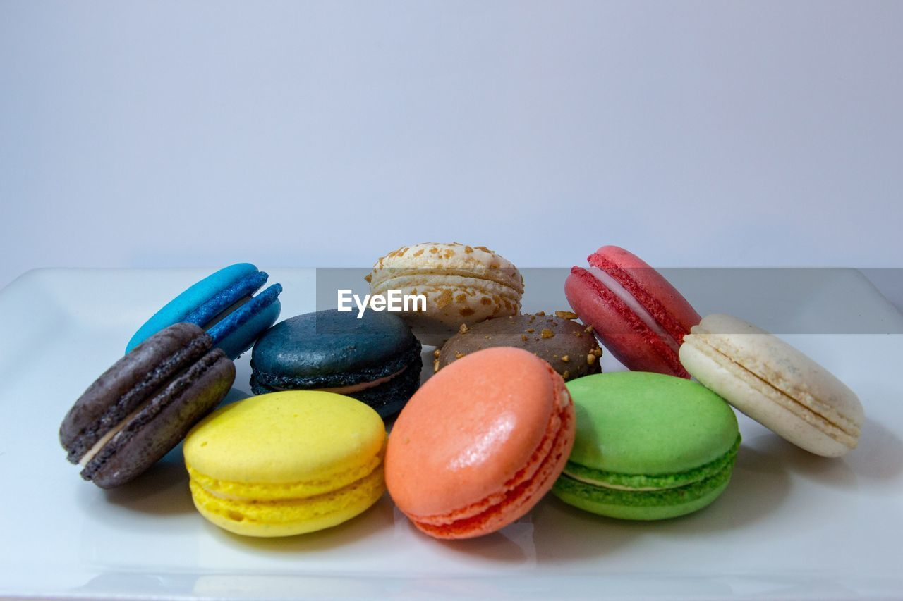 Multi colored macaroons against white background