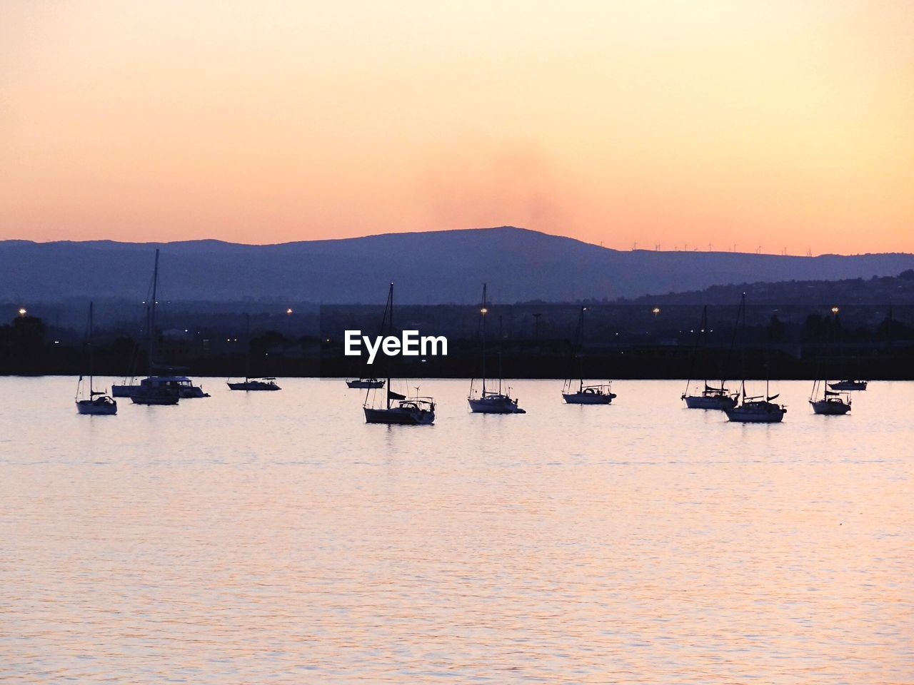 Nautical vessels on lake against mountain during sunset