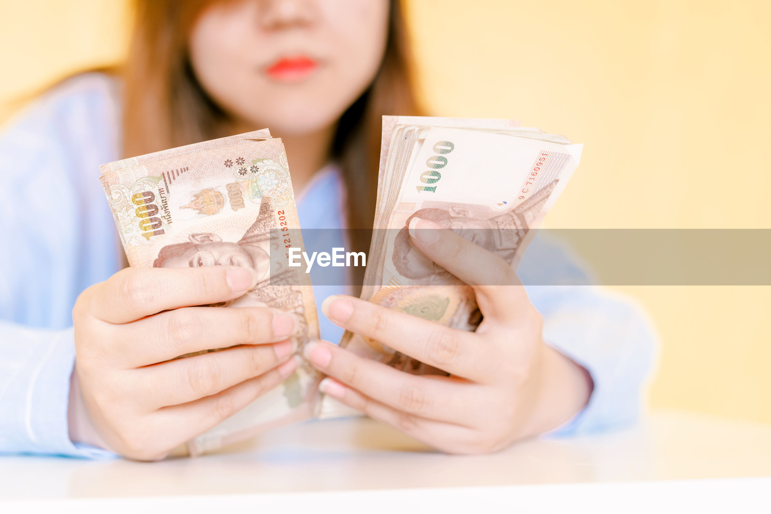 Midsection of woman counting paper currency on table