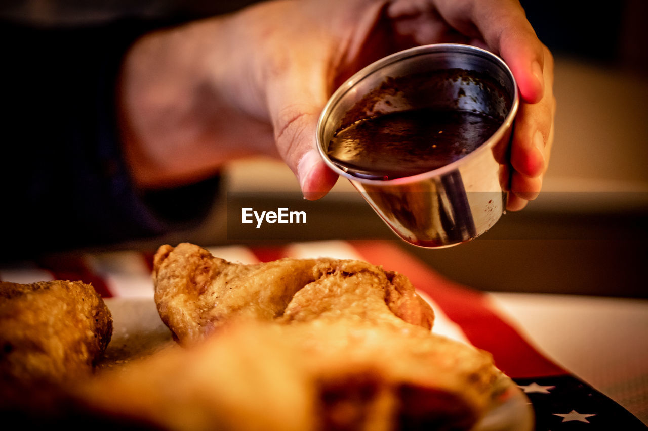 food and drink, human hand, hand, one person, human body part, real people, drink, food, freshness, indoors, selective focus, refreshment, holding, close-up, cup, lifestyles, mug, table, coffee cup, finger, breakfast, human limb, tea cup