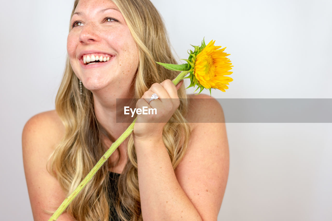 Close-up of woman looking away while holding flower
