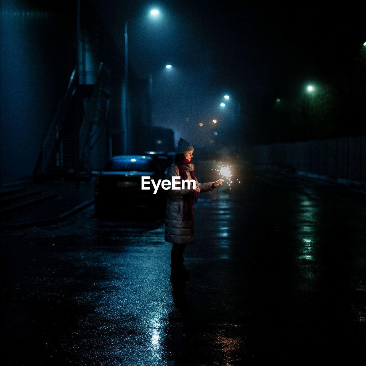 MAN STANDING IN ILLUMINATED NIGHT