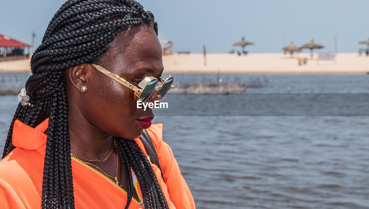 An african woman with round sunglasses from ghana is waiting for a boat on a sunny hot day in accra