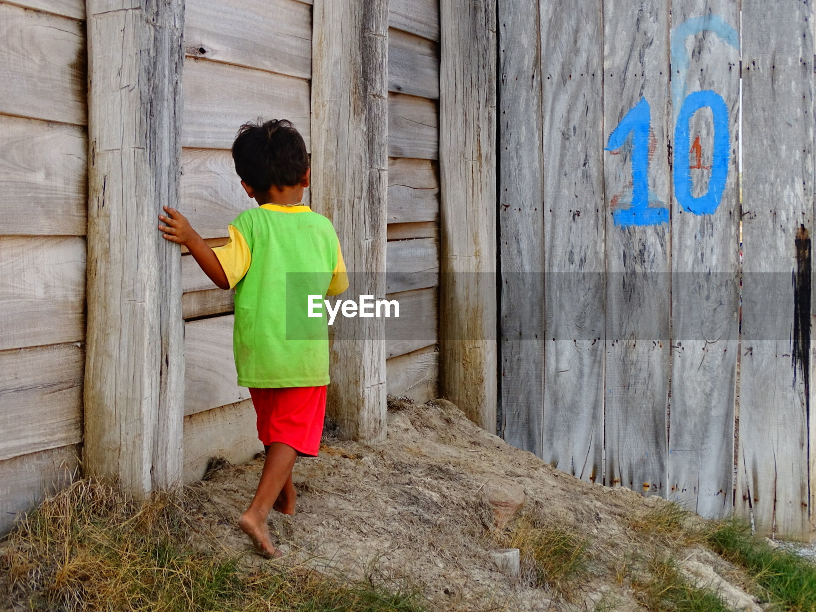 Rear view of child walking by wooden walls