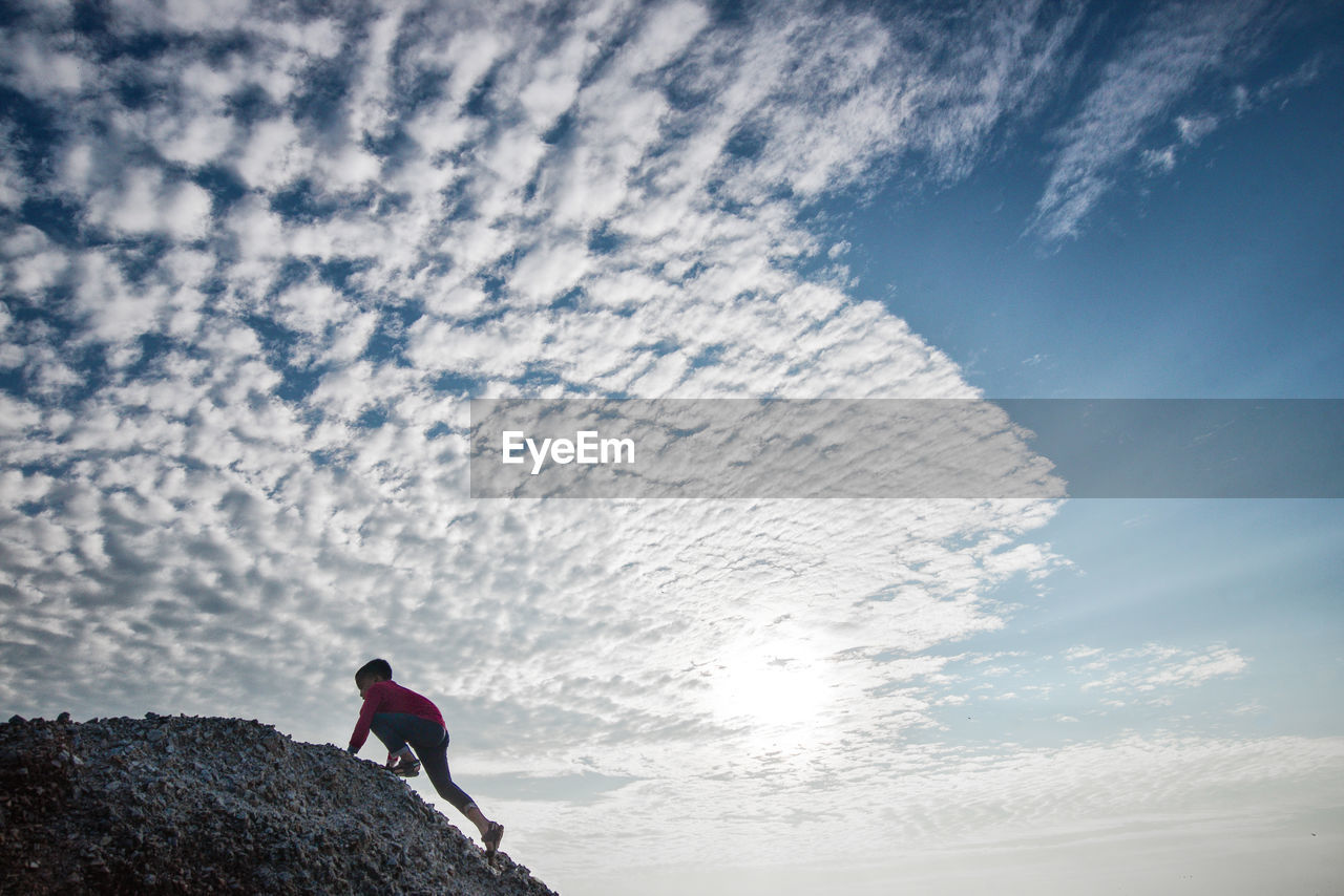 Side view of boy climbing mountain against cloudy sky