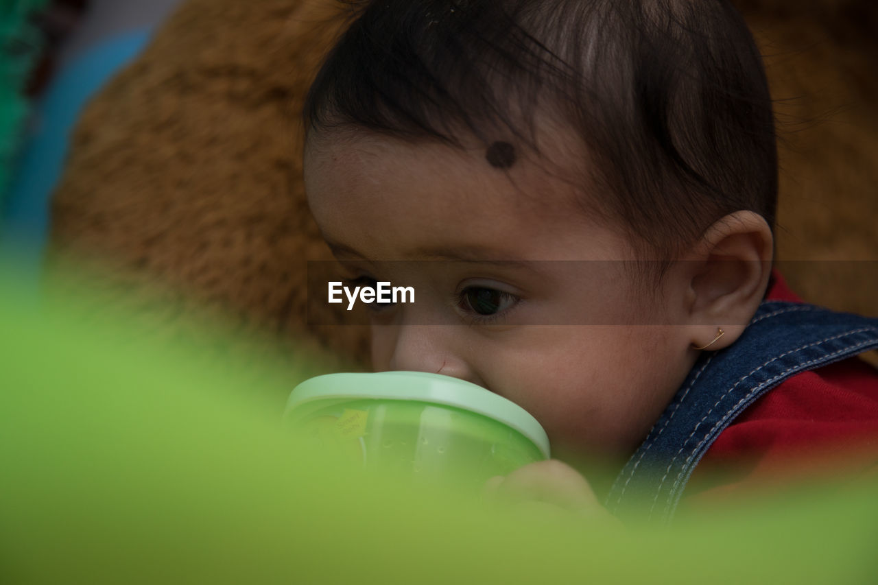 child, childhood, headshot, portrait, one person, real people, drink, boys, drinking, lifestyles, refreshment, males, food and drink, front view, men, cup, selective focus, innocence, human face