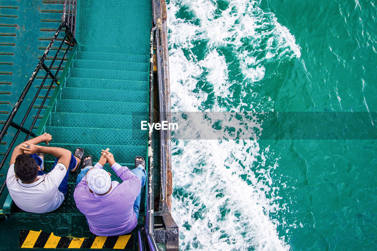 High Angle View Of Men Sitting In Ferry Sailing On Sea