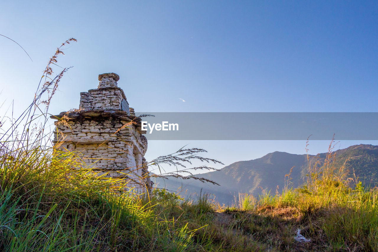 sky, plant, no people, nature, built structure, mountain, beauty in nature, architecture, scenics - nature, blue, environment, grass, tranquility, day, copy space, land, clear sky, building exterior, field, tranquil scene, outdoors, ancient civilization