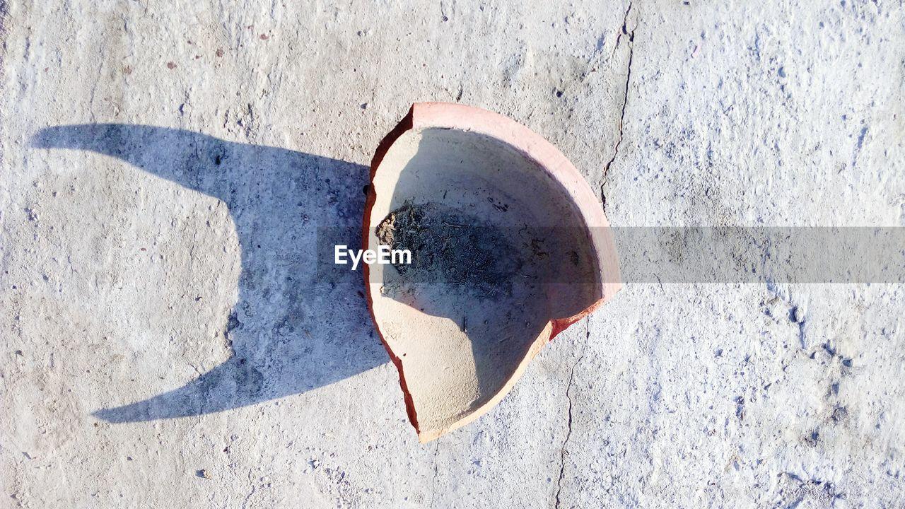 High angle view of broken earthen pot on floor