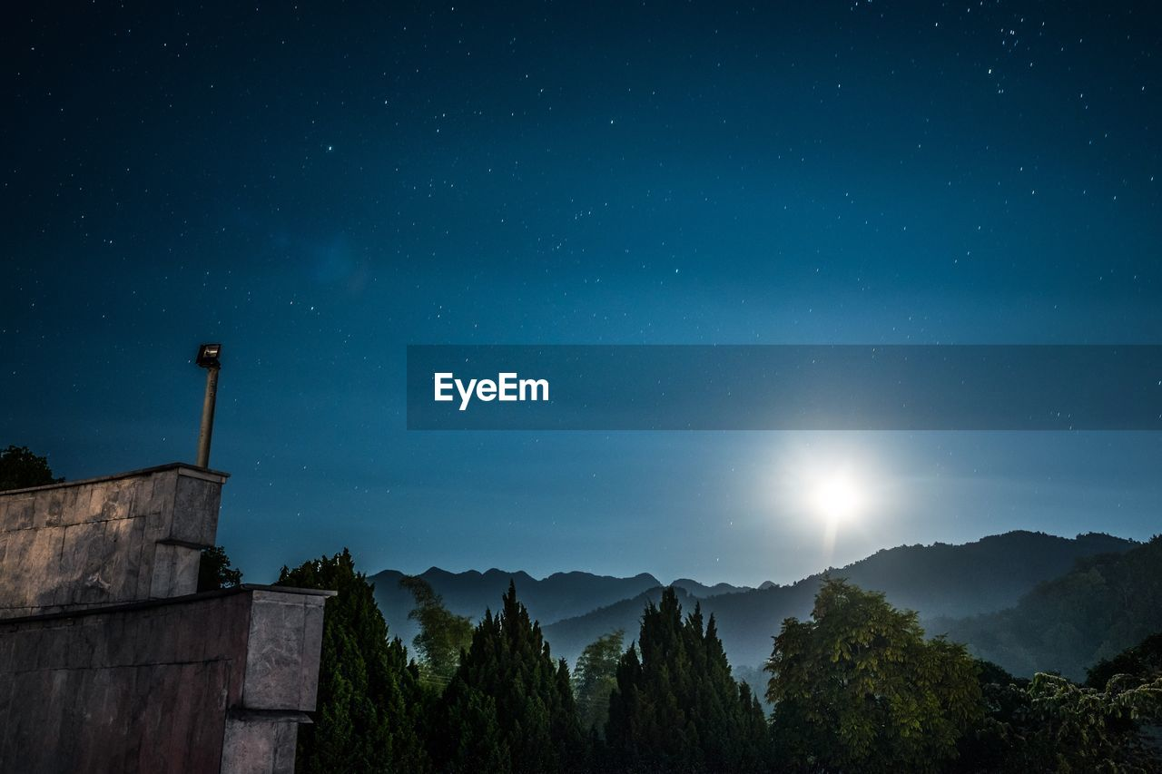 Low Angle View Of Trees And Mountain Against Sky At Night