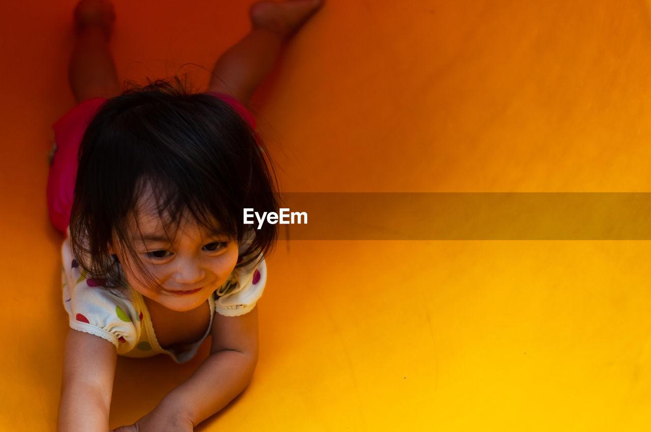 High angle view of cute girl lying on yellow slide