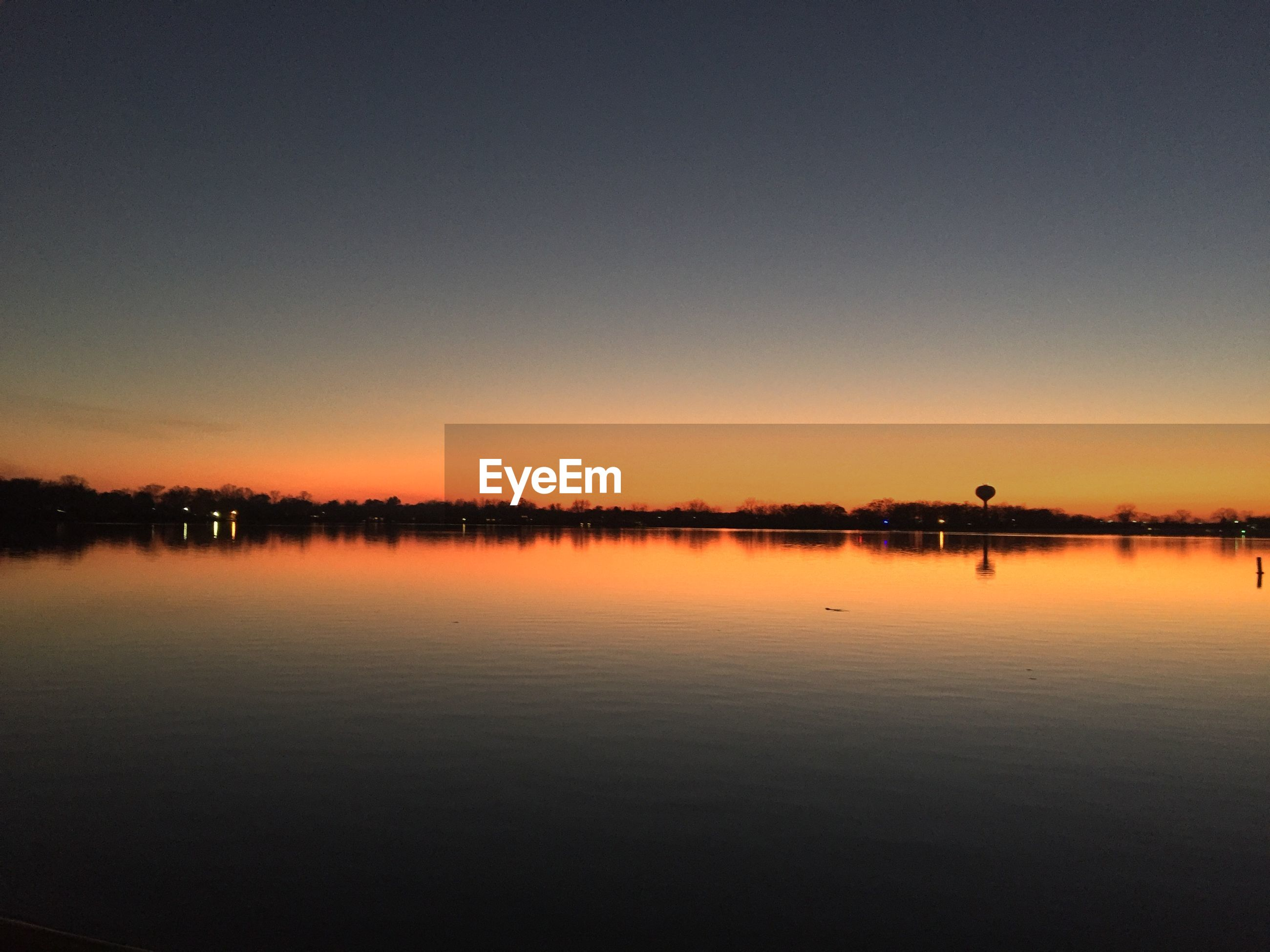 Scenic view of calm lake against clear sky during sunset