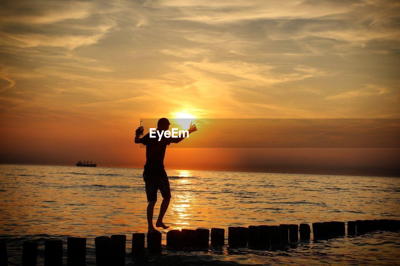 Silhouette Walking On Groyne In Sea Against Sky During Sunset