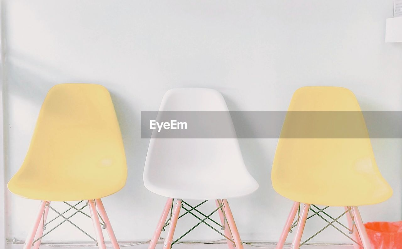 yellow, no people, side by side, indoors, seat, chair, table, absence, group of objects, wall - building feature, lighting equipment, still life, multi colored, close-up, choice, in a row, medium group of objects, variation, home interior, arrangement, electric lamp