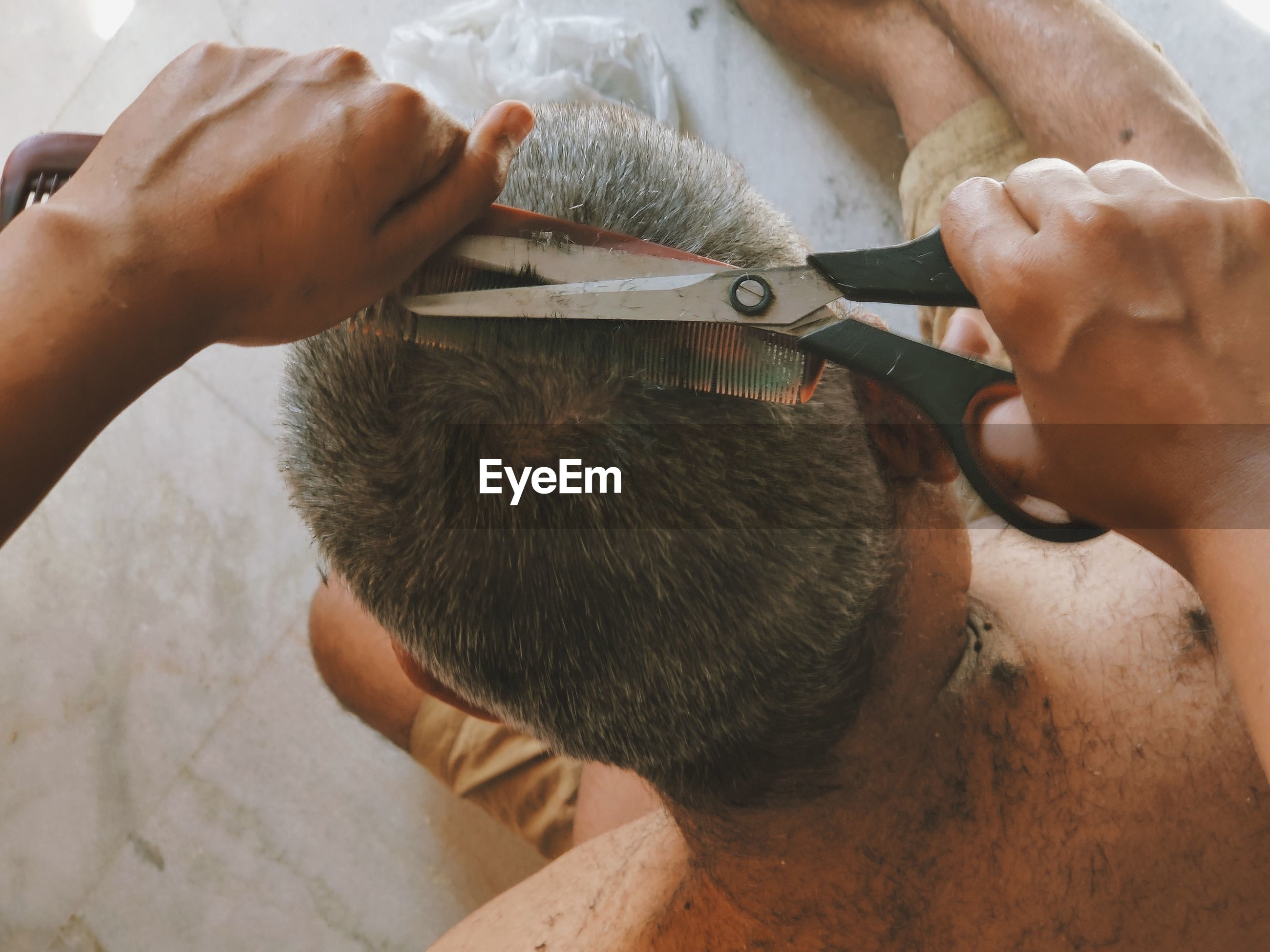 High angle view of man working/ grooming hair