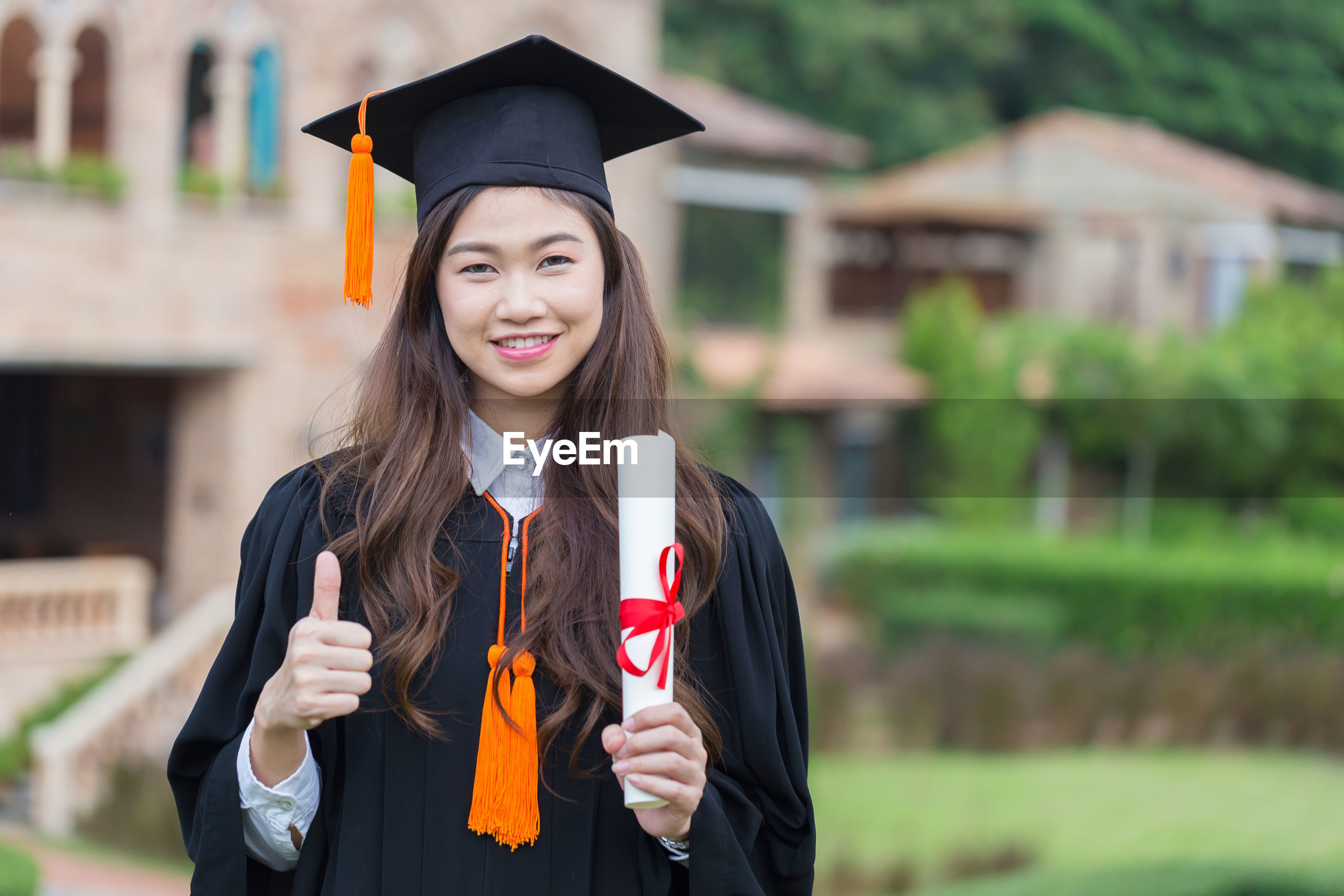 Portrait of young woman wearing graduation gown holding paper while standing outdoors