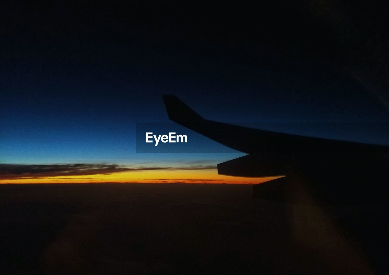 airplane, silhouette, transportation, air vehicle, nature, sky, airplane wing, beauty in nature, blue, sunset, journey, outdoors, scenics, no people, aircraft wing, landscape, flying, clear sky, day