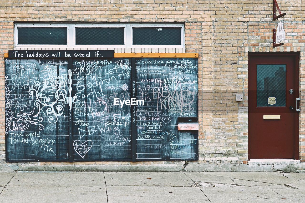 graffiti, architecture, text, built structure, wall - building feature, building exterior, brick wall, blackboard, day, no people, outdoors, window, communication, technology