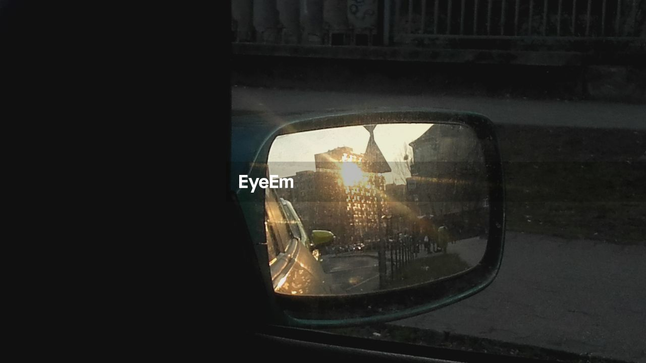 window, glass - material, side-view mirror, transportation, lens flare, reflection, car, sunset, sun, mode of transport, land vehicle, built structure, sunlight, travel, indoors, architecture, no people, illuminated, day, nature, close-up, city, sky