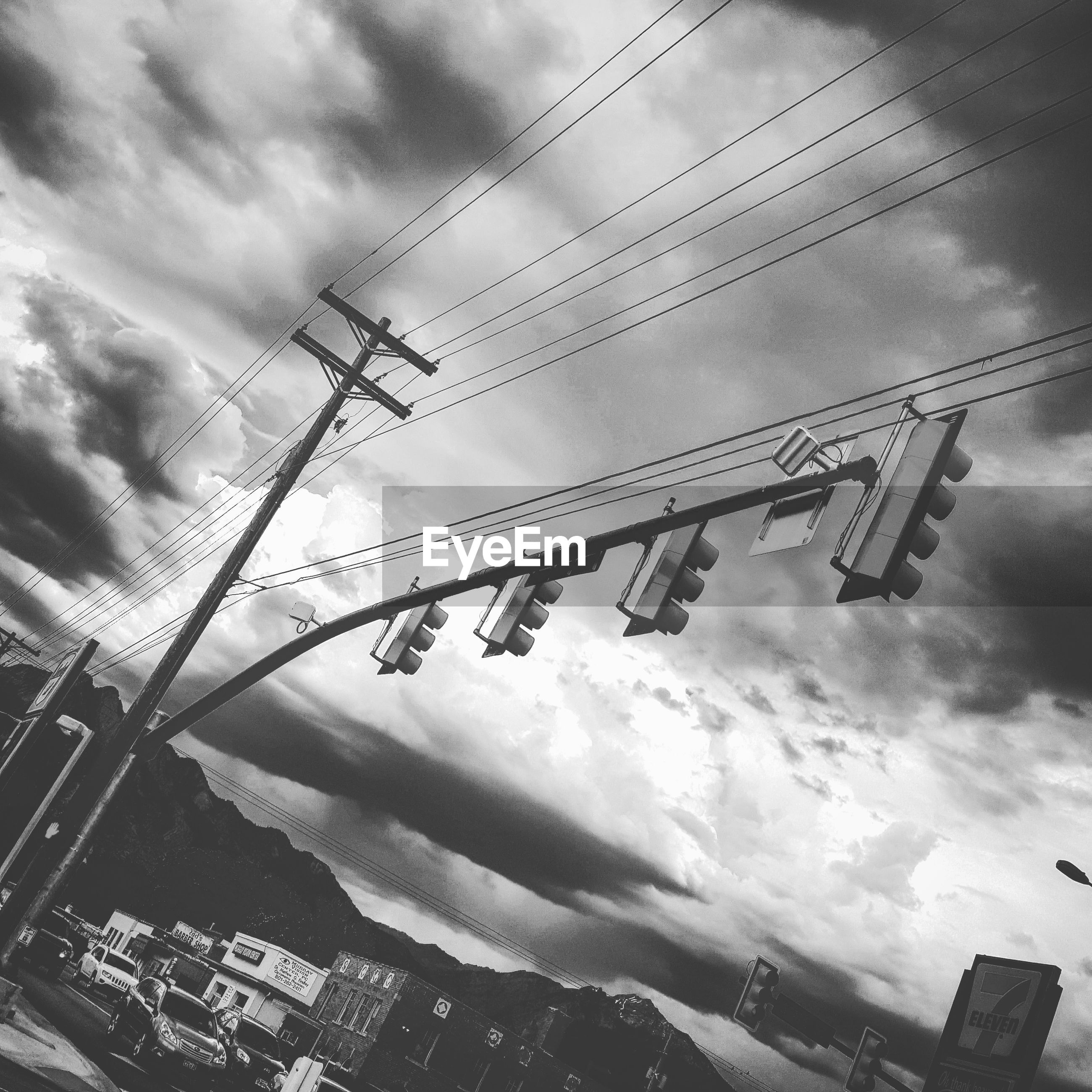 low angle view, sky, text, cloud - sky, hanging, communication, cloudy, built structure, outdoors, building exterior, day, architecture, no people, western script, cable, tilt, cloud, weather, electricity, high section