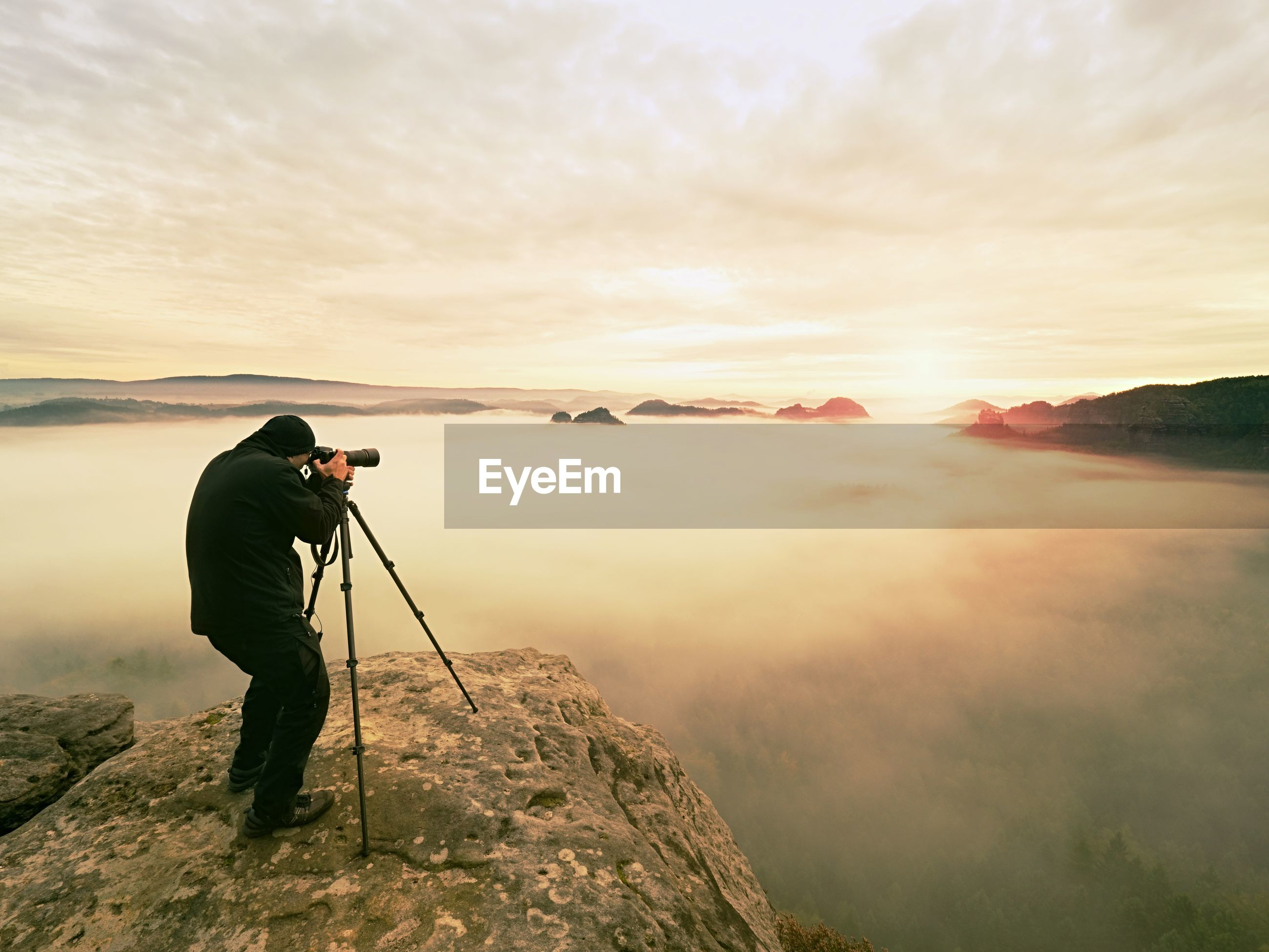 MAN PHOTOGRAPHING ON MOUNTAIN AGAINST SKY AT SUNSET