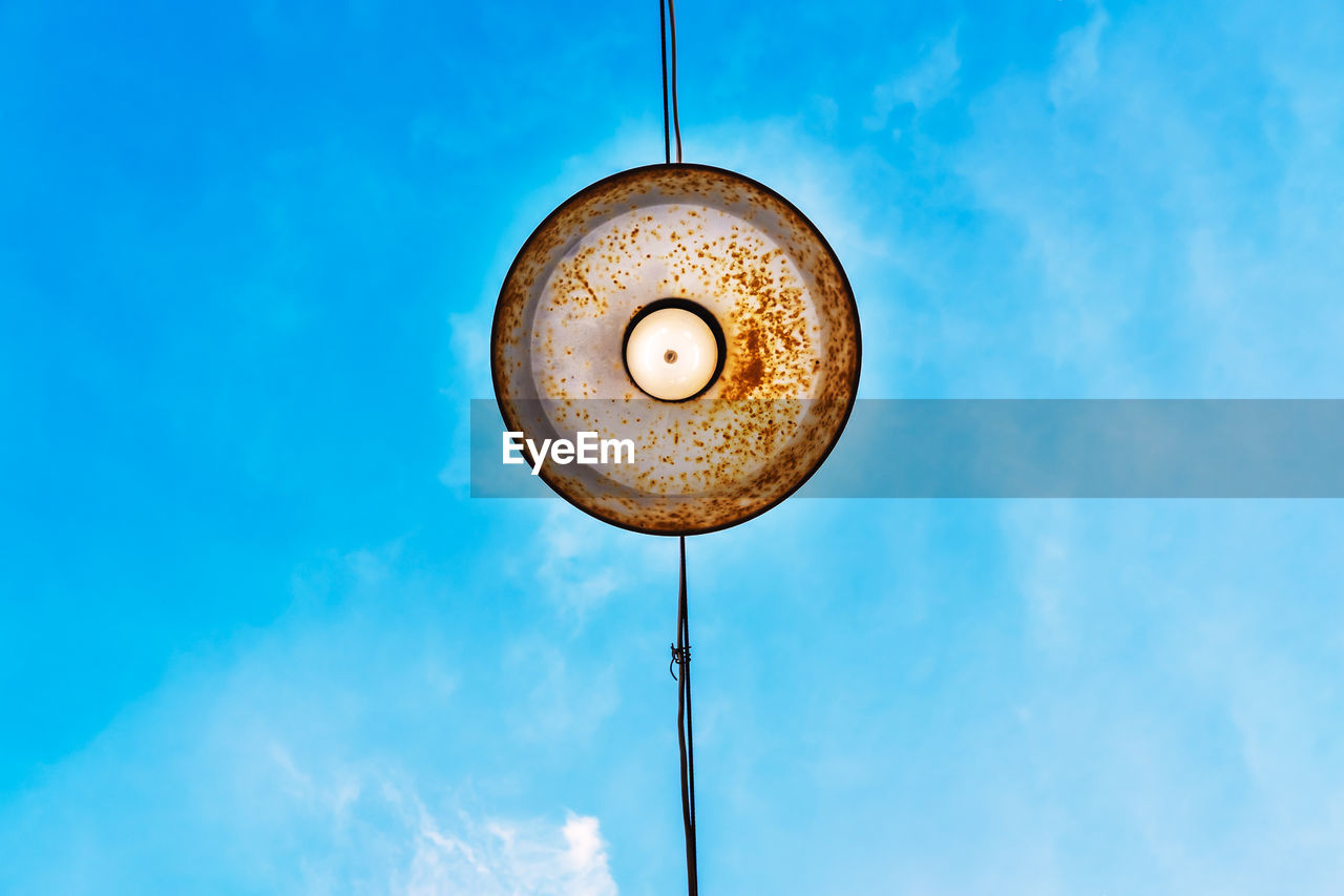 Low angle view of pendant light hanging against blue sky