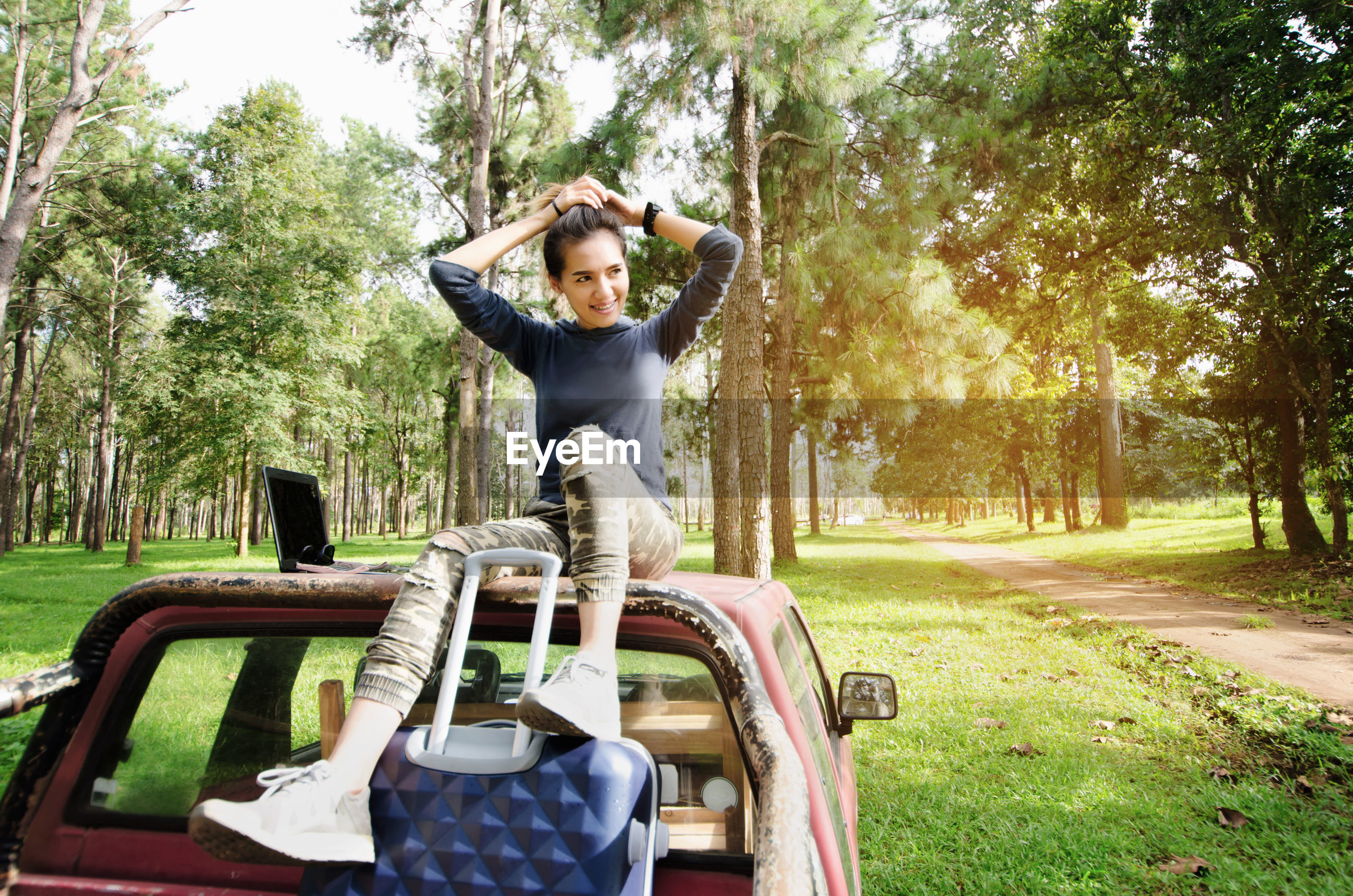 Woman sitting on car in forest