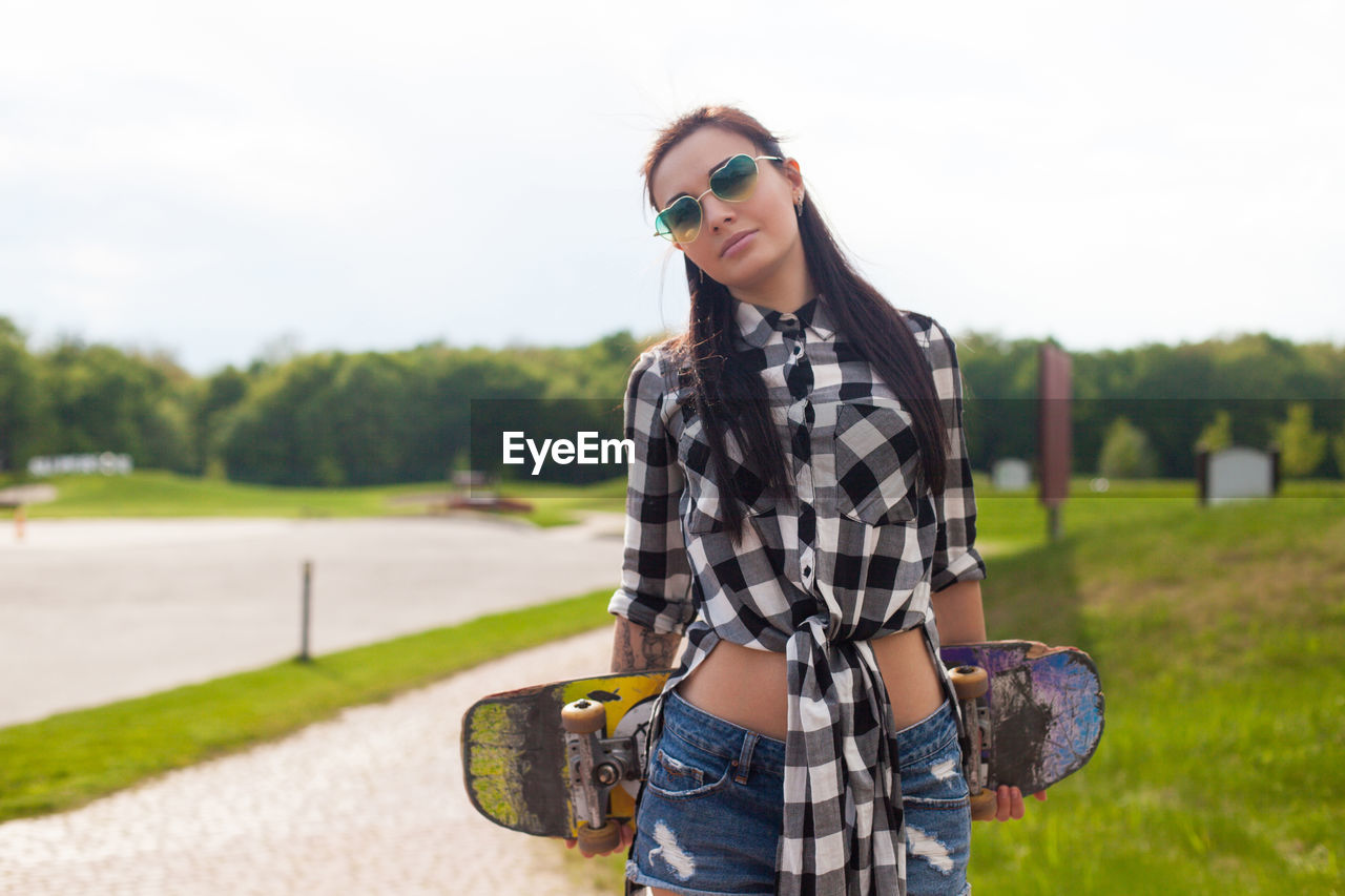 glasses, one person, standing, casual clothing, looking at camera, young adult, portrait, sunglasses, focus on foreground, real people, young women, lifestyles, fashion, leisure activity, smiling, front view, three quarter length, hair, nature, hairstyle, beautiful woman, outdoors