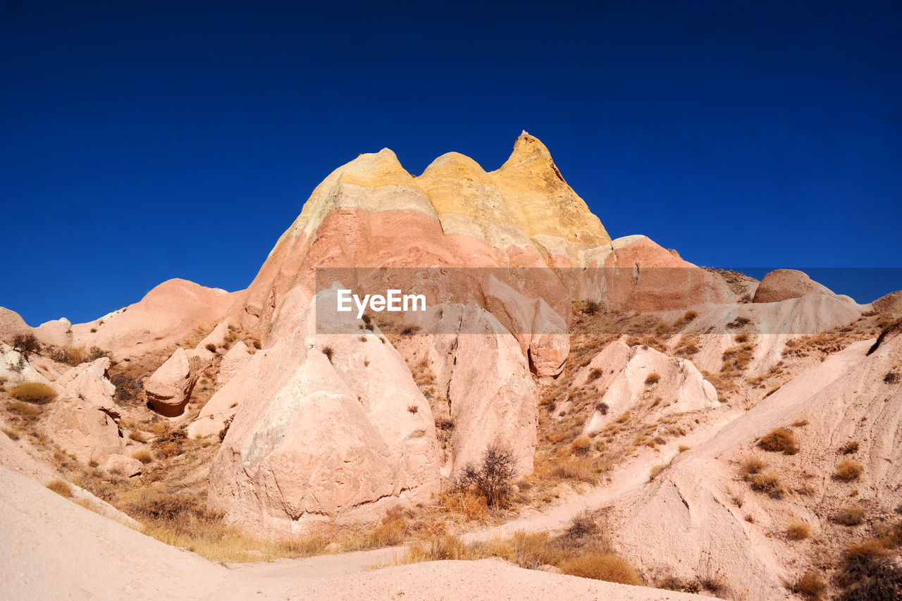 Rock formations in desert against blue sky