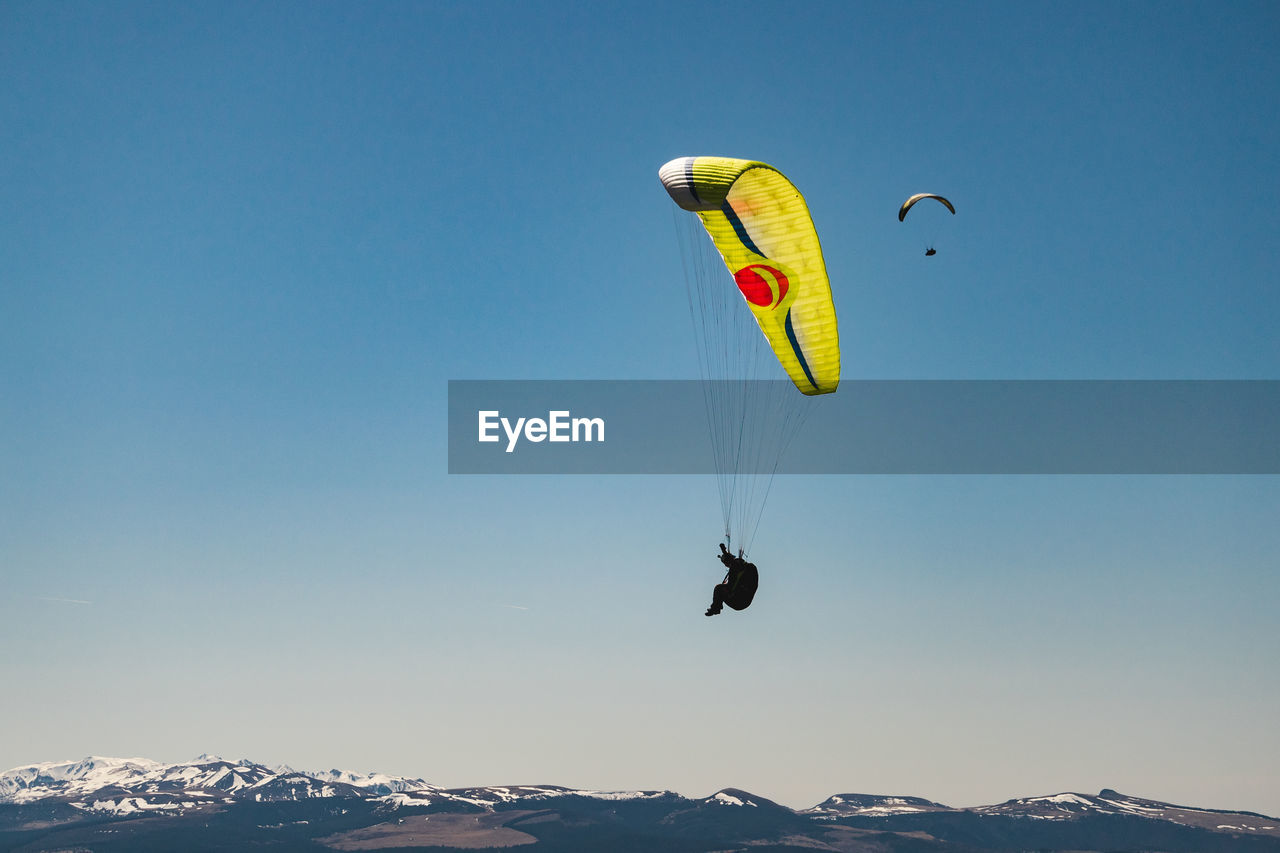 extreme sports, sport, sky, mid-air, adventure, parachute, paragliding, leisure activity, real people, flying, unrecognizable person, clear sky, one person, joy, mountain, lifestyles, nature, exhilaration, beauty in nature, day, freedom, mountain range, outdoors, snowcapped mountain