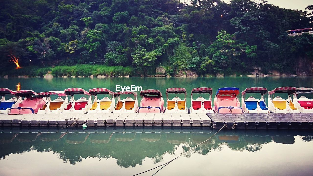 water, nautical vessel, reflection, tree, in a row, no people, transportation, day, moored, outdoors, lake, pedal boat, waterfront, mode of transport, nature