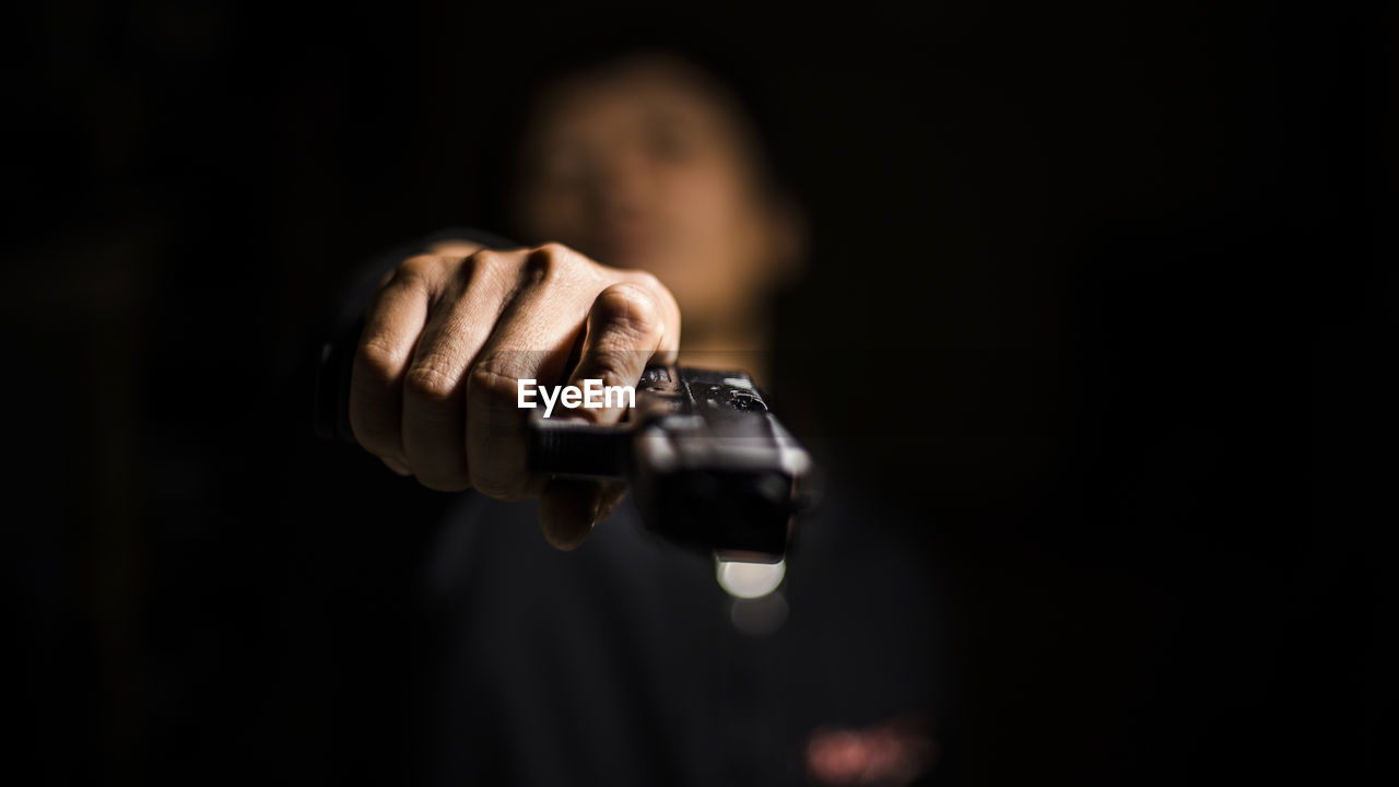 Close-Up Of Man Holding Gun In Darkroom