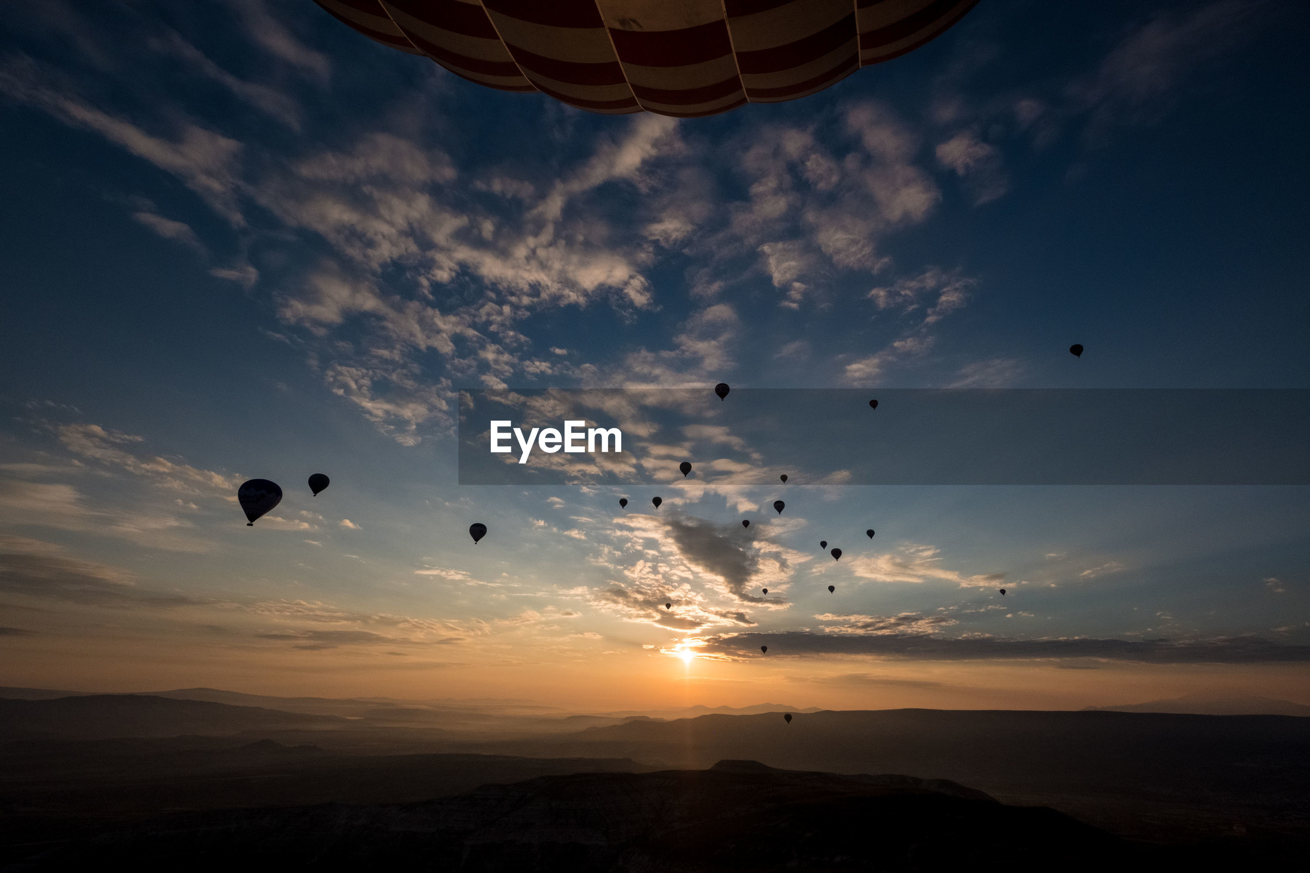 Low angle view of hot air balloons against sky during sunrise