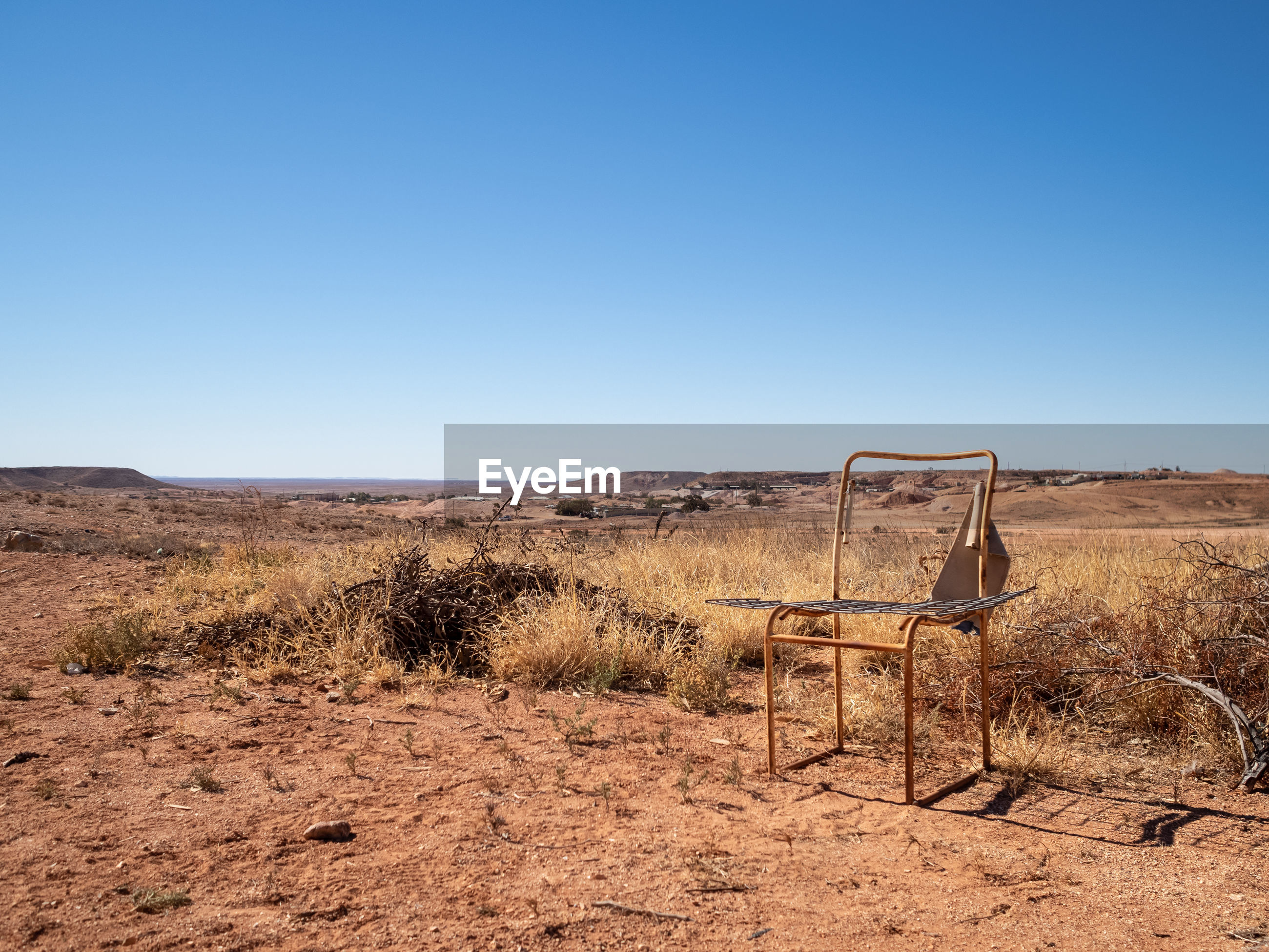Scenic view of .ry arid landscape against clear blue sky with old seat frame in foreground