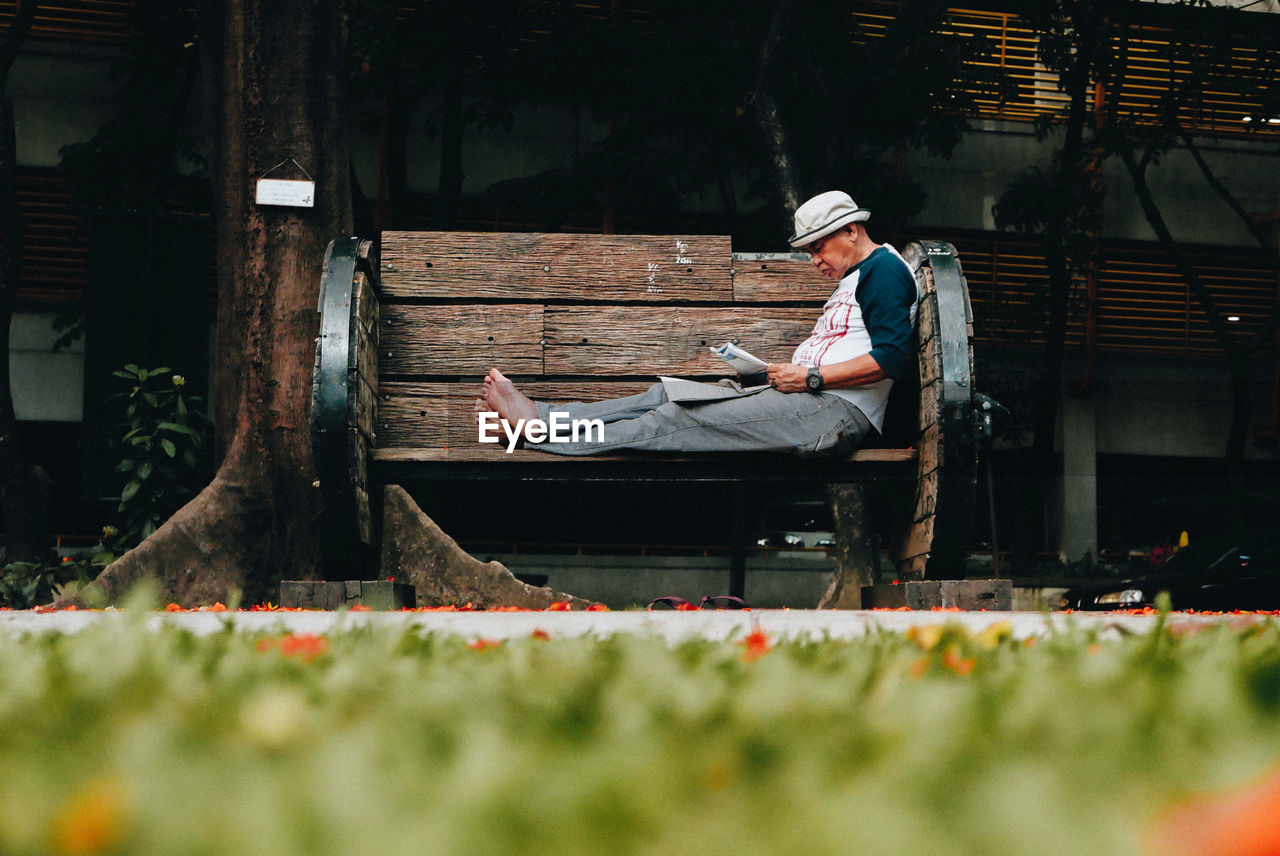 Side view of man reading newspaper on bench at park
