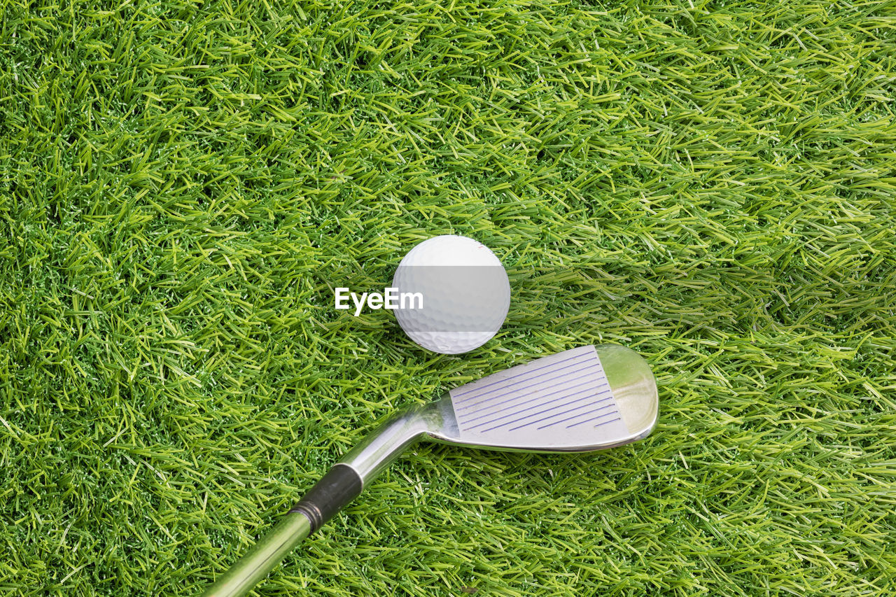 grass, golf, green color, ball, activity, plant, sport, golf course, golf ball, high angle view, green - golf course, day, no people, leisure activity, nature, golf club, still life, outdoors, land, sports equipment