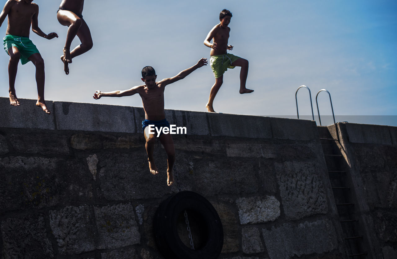 real people, jumping, mid-air, togetherness, outdoors, full length, leisure activity, day, childhood, sky, fun, lifestyles, boys, friendship, men, stunt, people