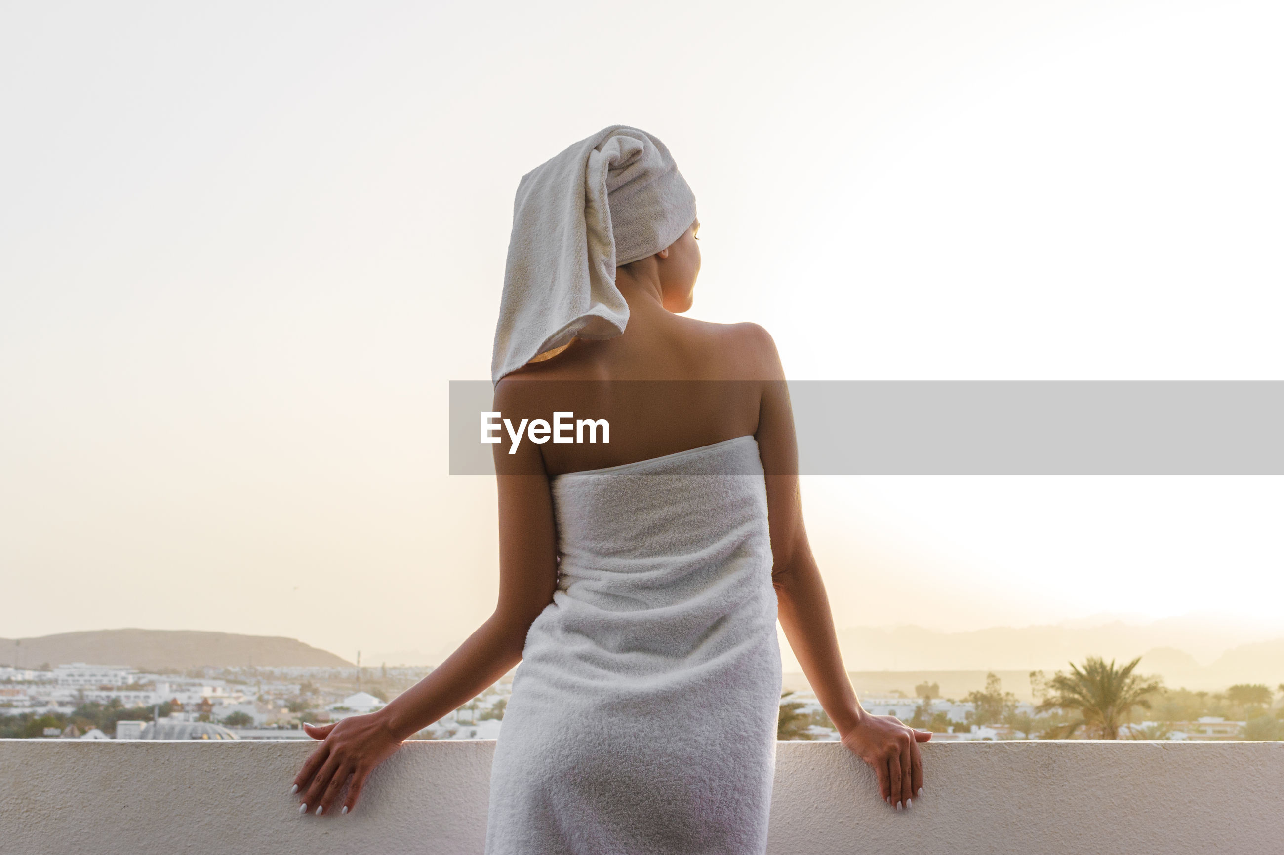 Young woman wrapped in towels at city against clear sky